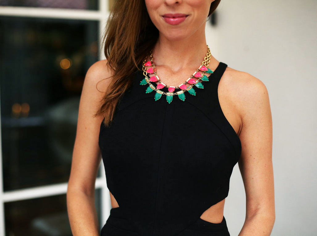 Bright necklace, black jumpsuit with cut-outs