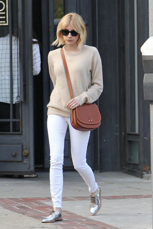 Emma Roberts pairs a camel sweater with white skinny jeans and silver oxfords.