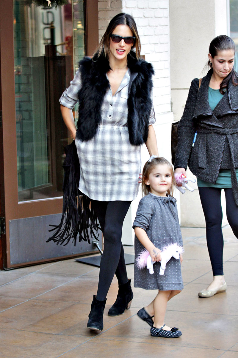Alessandra Ambrosio wears a plaid shirtdress with a fur vest, opaque tights and Western style ankle booties.