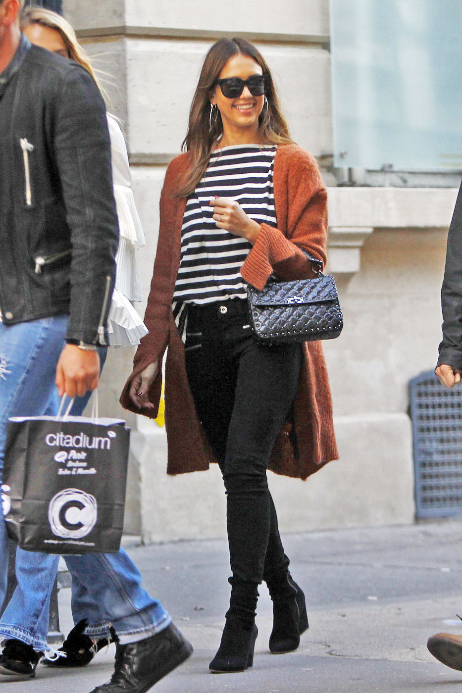 Jessica Alba wears a stripe top, zipper front skinny jeans and a rust colored cardigan while out and about in Paris.