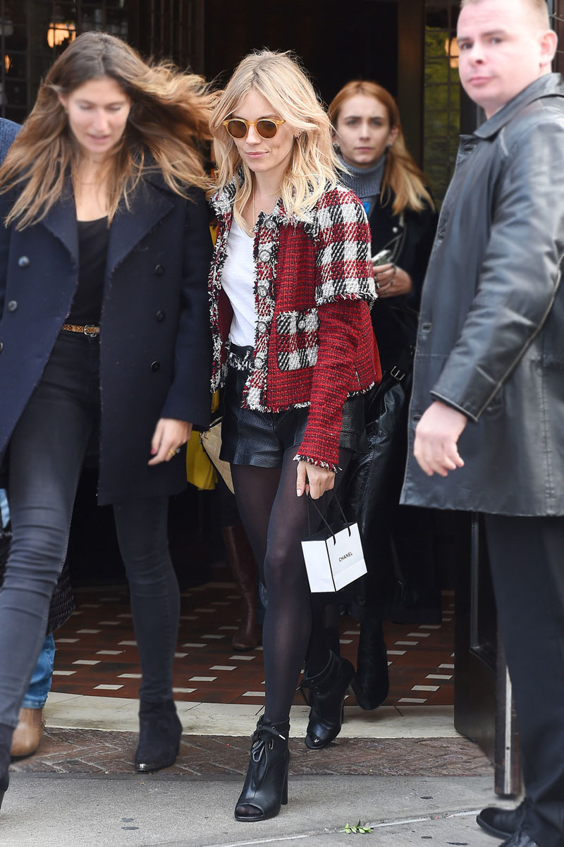Sienna Miller wears a plaid tweed jacket with leather shorts and peep toe booties.