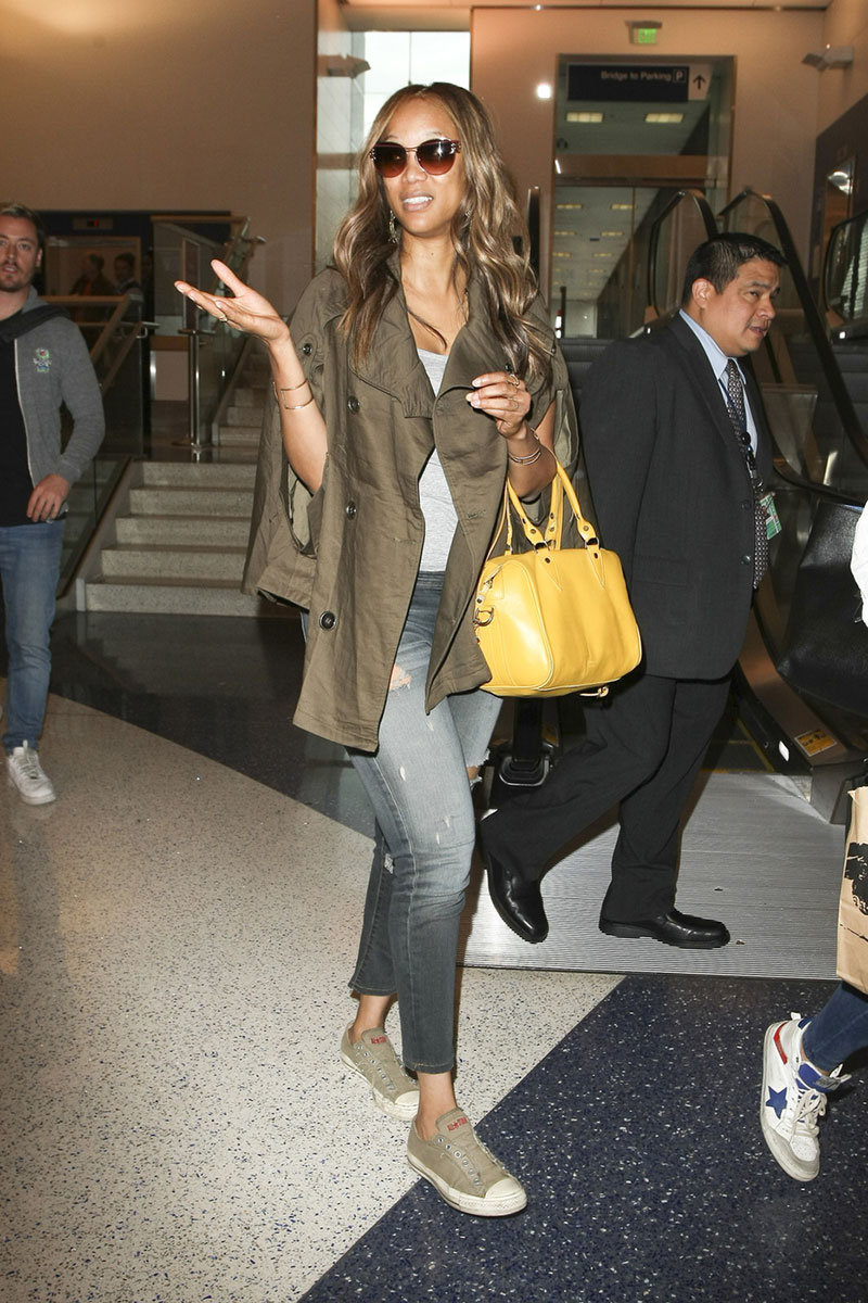 Tyra Banks wears a trench cape jacket and Converse sneakers while traveling.