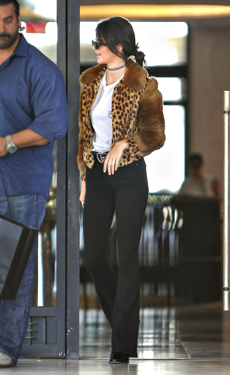 Kendall Jenner wears a leopard jacket with black flare pants and patent ankle booties.