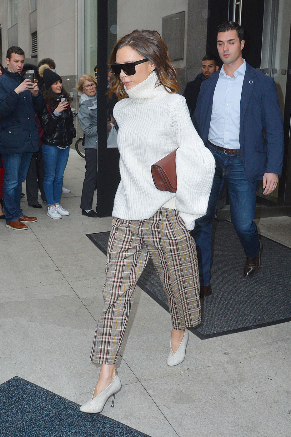 Victoria Beckham steps out in a turtleneck sweater and check pants.