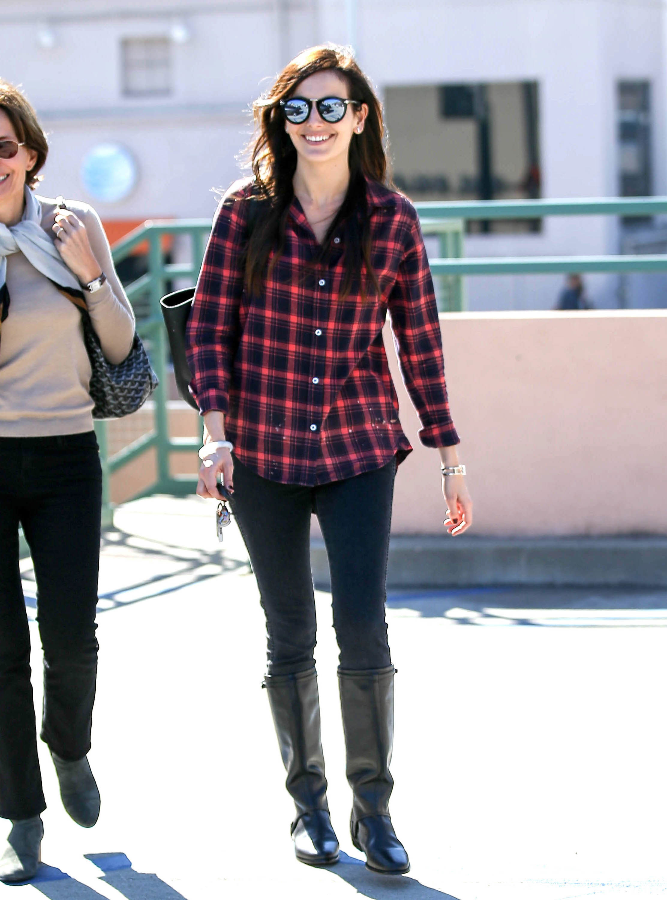 Camilla Belle looks casual and chic in a plaid shirt with black leggings and black riding boots.