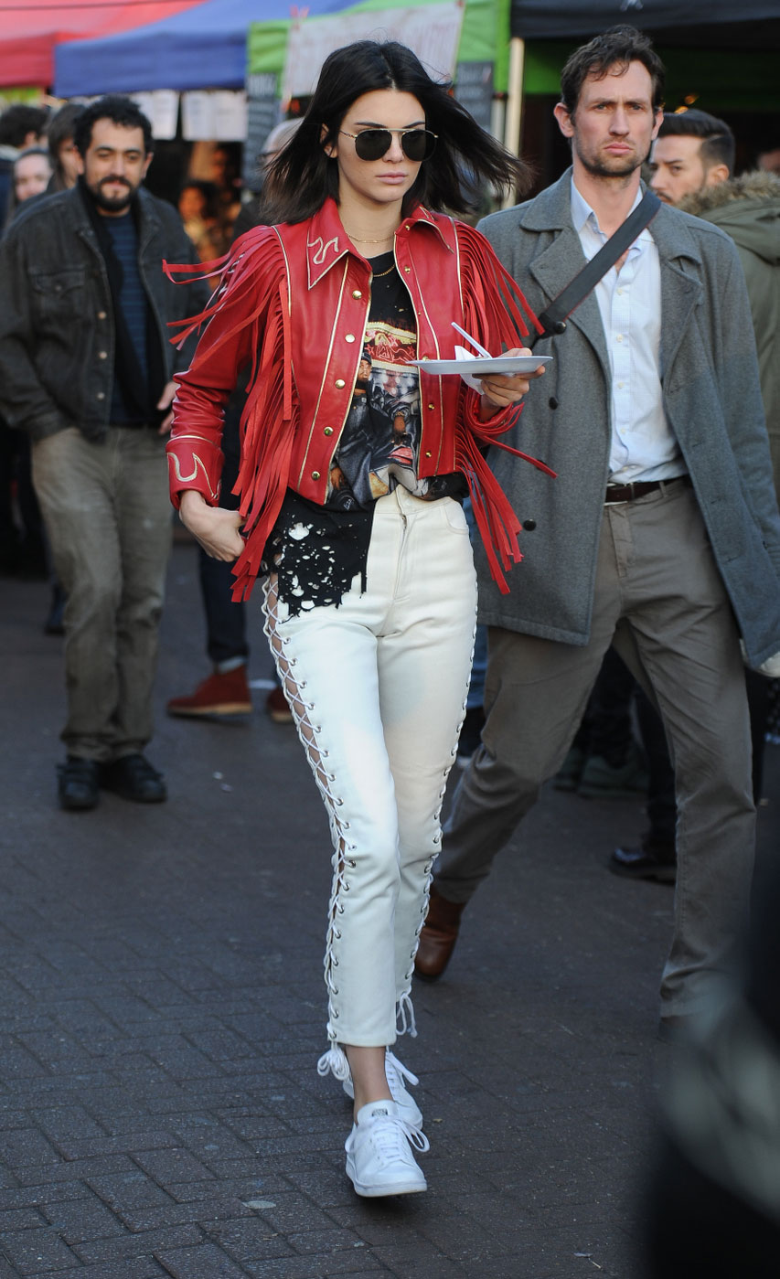 Kendall Jenner explores Portabello Market in London wearing a red leather jacket and white lace-up leather pants.