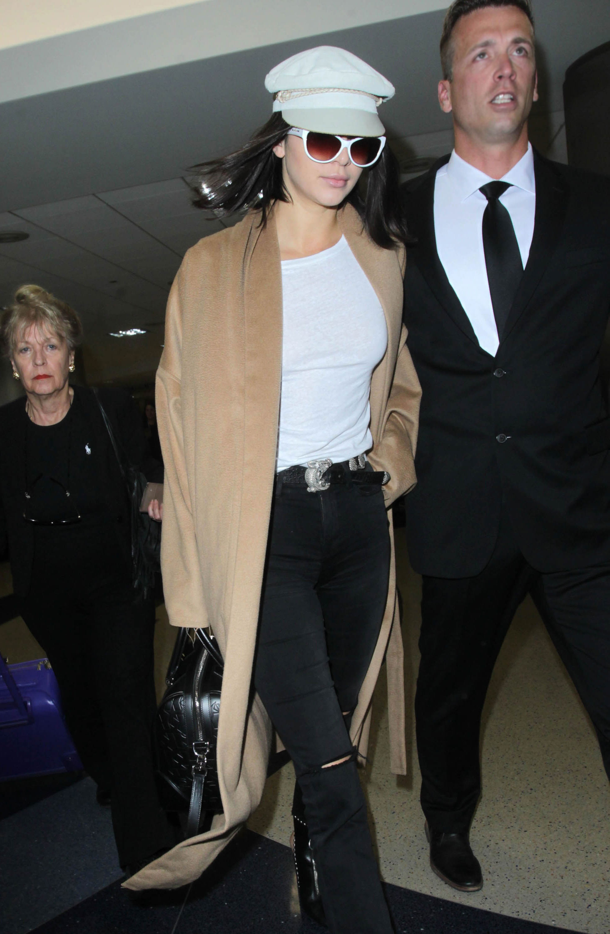 Kendall Jenner looks cool and effortless in a white tee, black ripped jeans and camel duster.