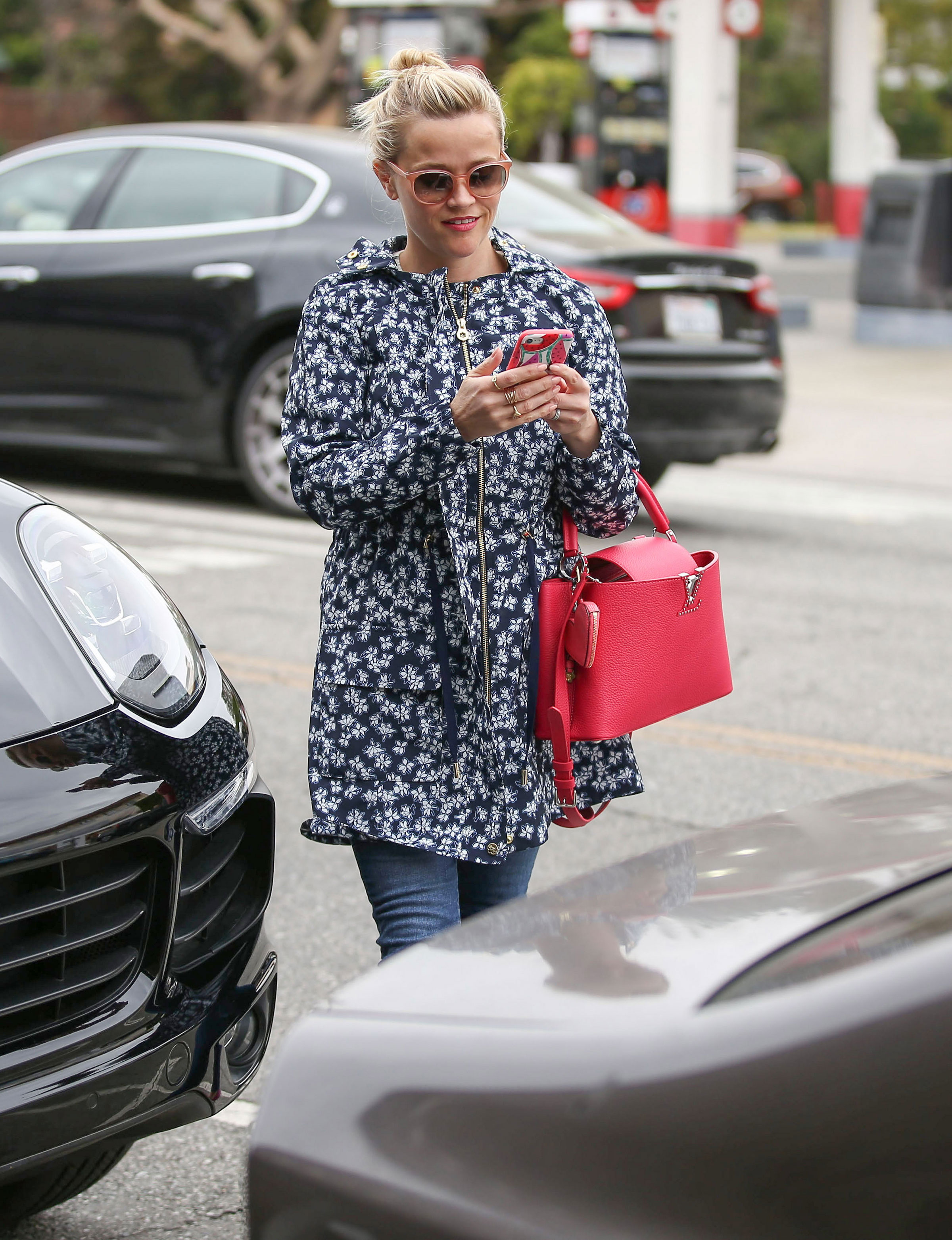 Reese Witherspoon stays stylish in the rain in a floral Draper James jacket.
