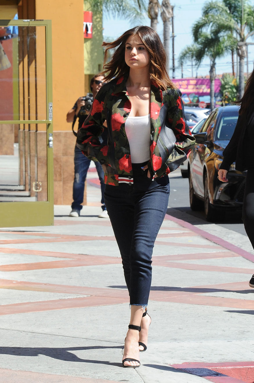 Selena Gomez slays in a red rose bomber jacket and ankle strap heels.