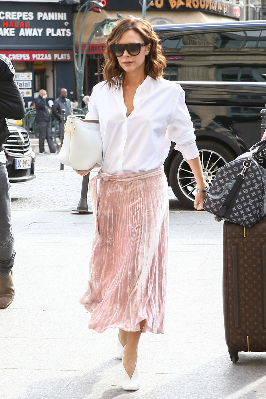 Victoria Beckham looks lovely in a pink pleated skirt and white blouse.