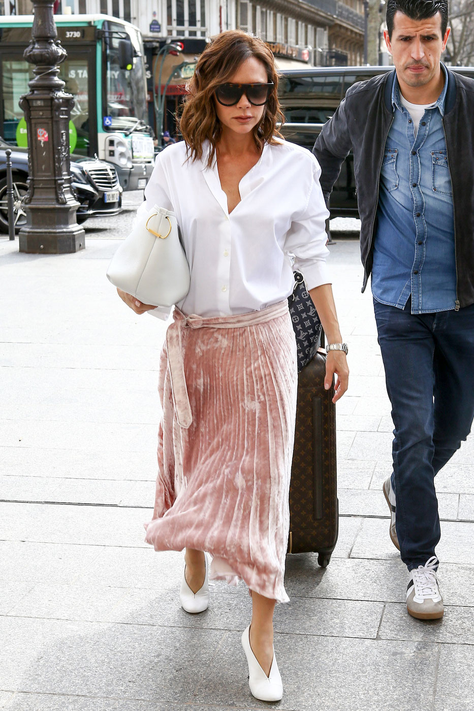 Victoria Beckham wears a pink pleated skirt and white blouse in Paris