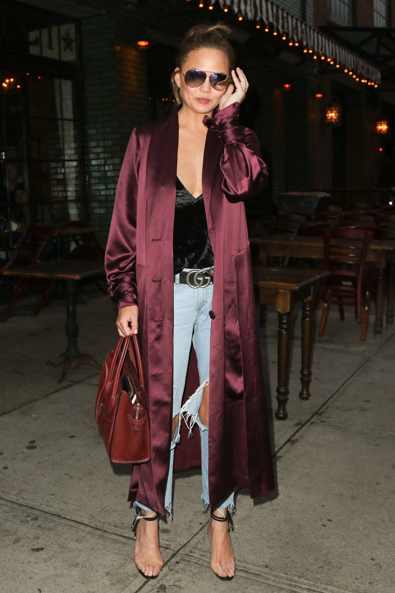 Chrissy Teigen steps out in a burgundy satin duster, ripped jeans and clear strap heels.