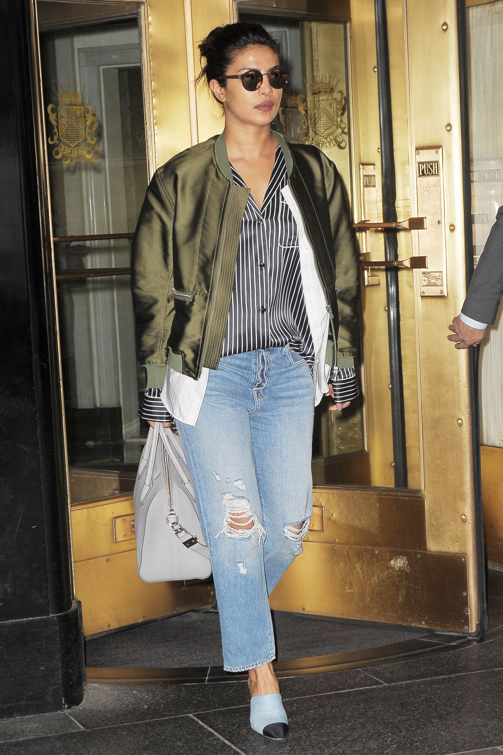 Priyanka Chopra looks chic in an olive bomber jacket, stripe blouse and crop high waist denim.