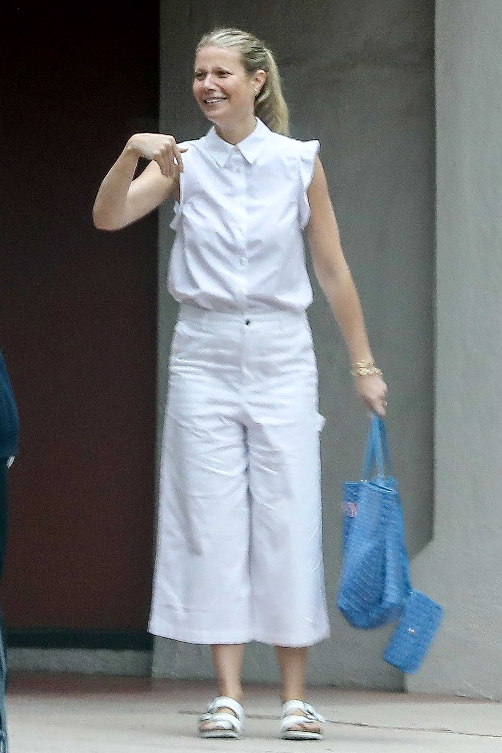 Gwyneth Paltrow wears a white sleeveless button shirt and wide leg crop pants plus white Birkenstock sandals.