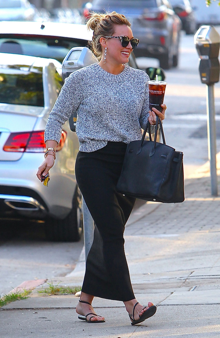 Hilary Duff has the best mom-on-the-go style in her black maxi skirt and Ancient Greek sandals.