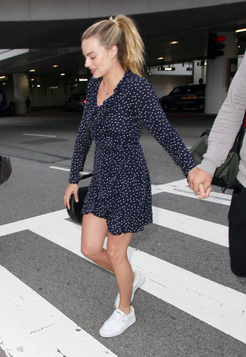 Margot Robbie looks chic in a retro-minded polka dot dress and modern white sneakers.