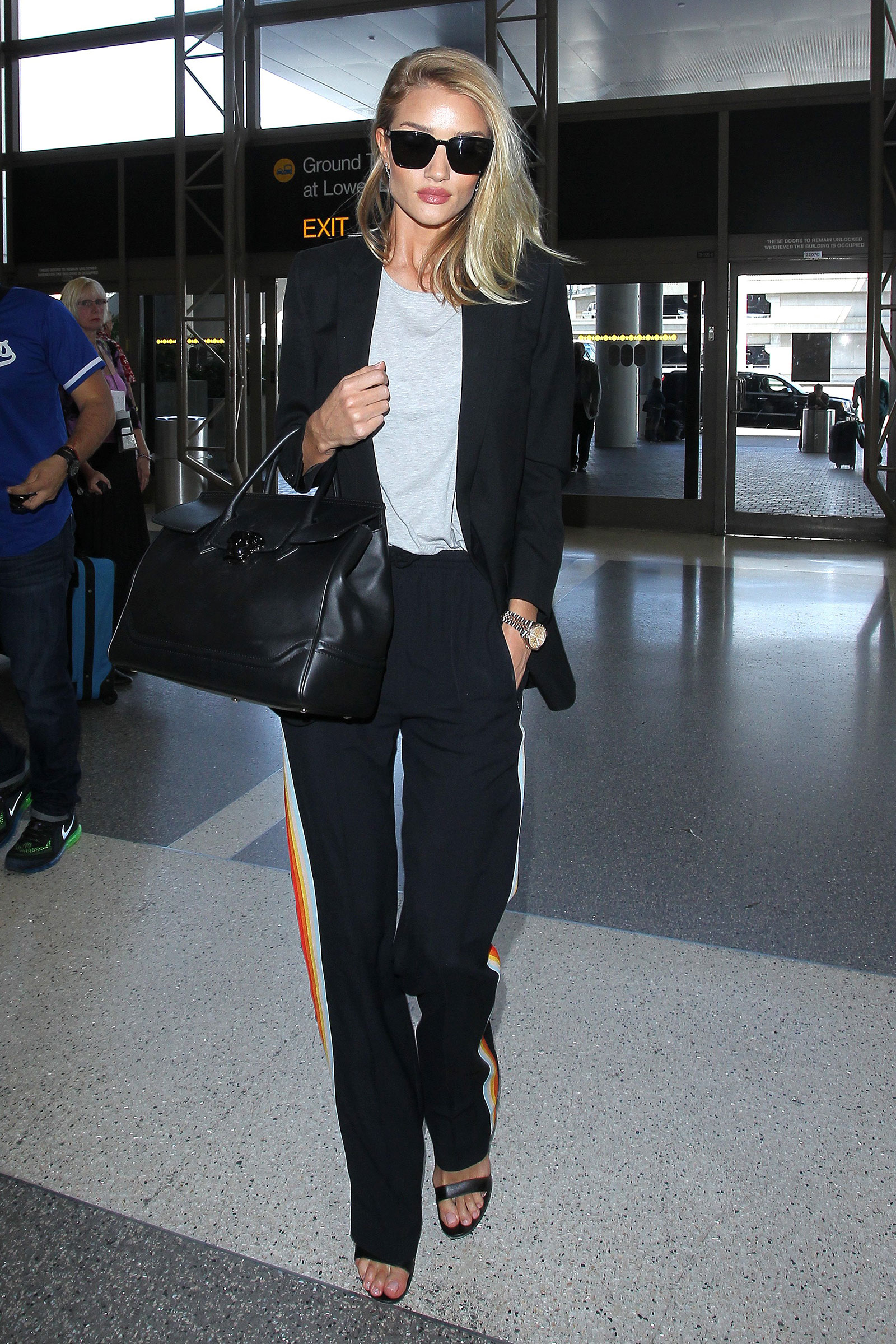 Rosie Huntington Whiteley wears track pants with heels and a blazer.