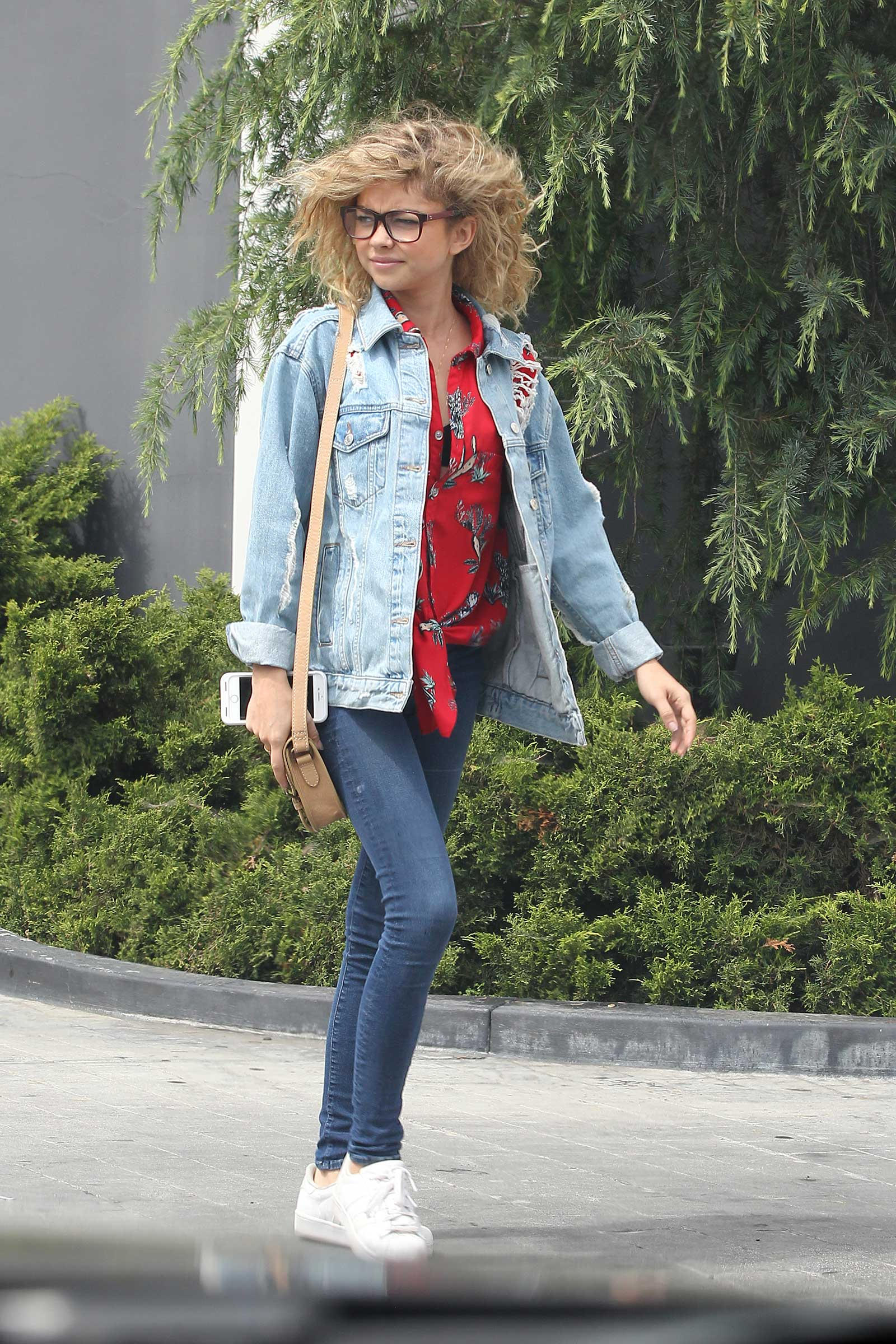 Sarah Hyland is cute and casual in a jean jacket, red print shirt and white sneakers.