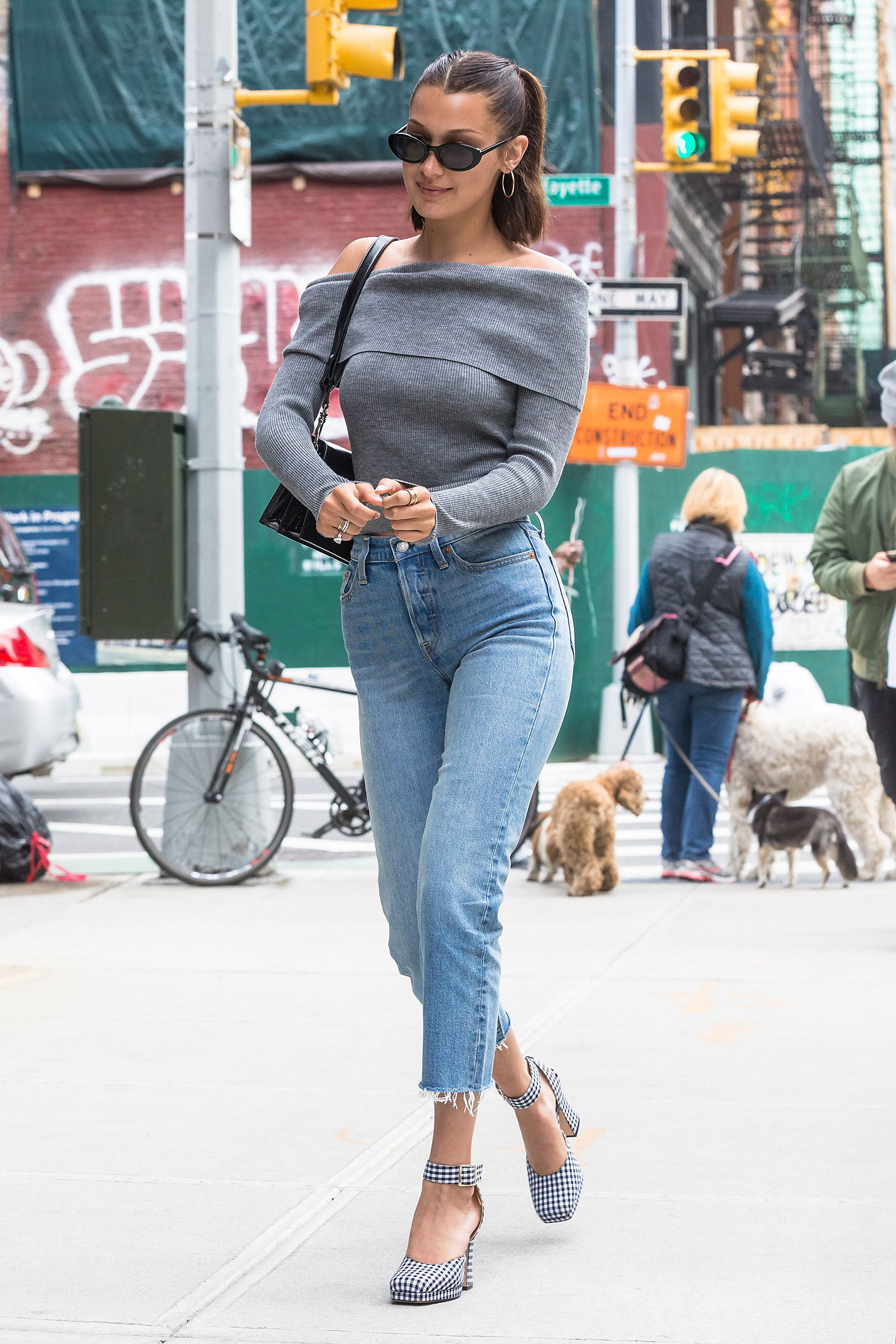 Bella Hadid looks cute and casual in a gray off the shoulder sweater, high waist jeans and gingham platform pumps.