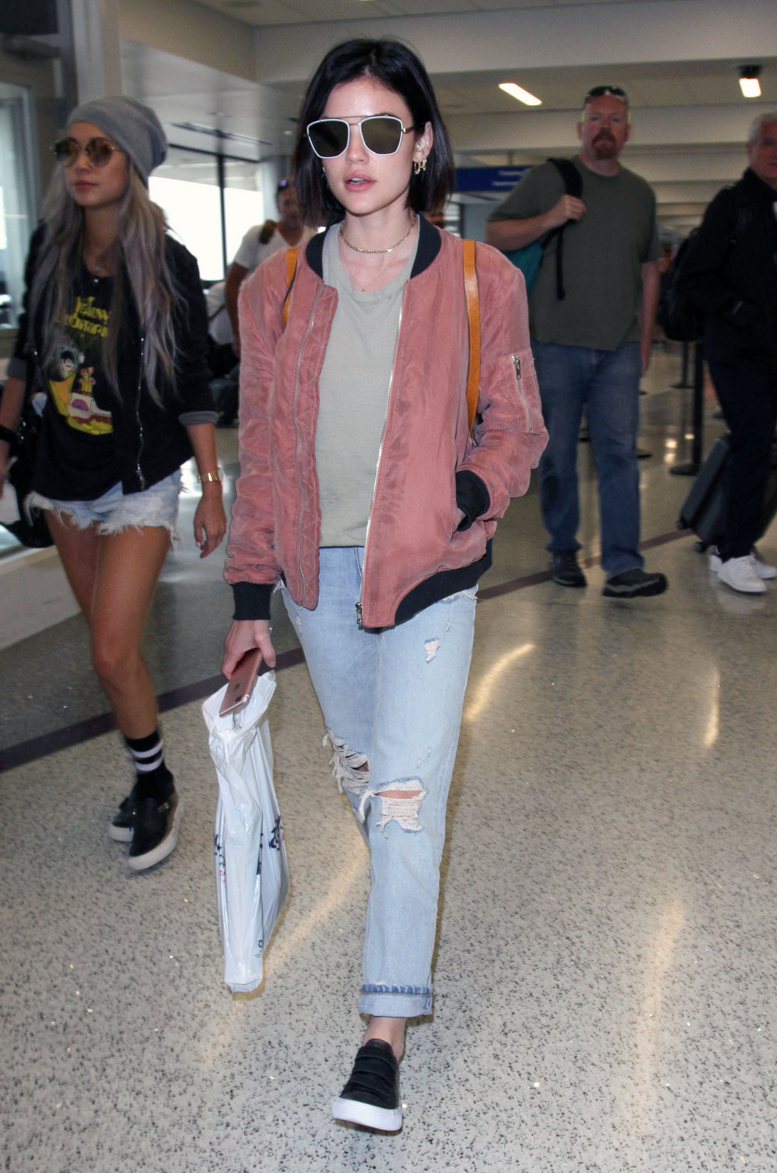 Lucy Hale's airport style is a comfy blush pink bomber and boyfriend jeans.