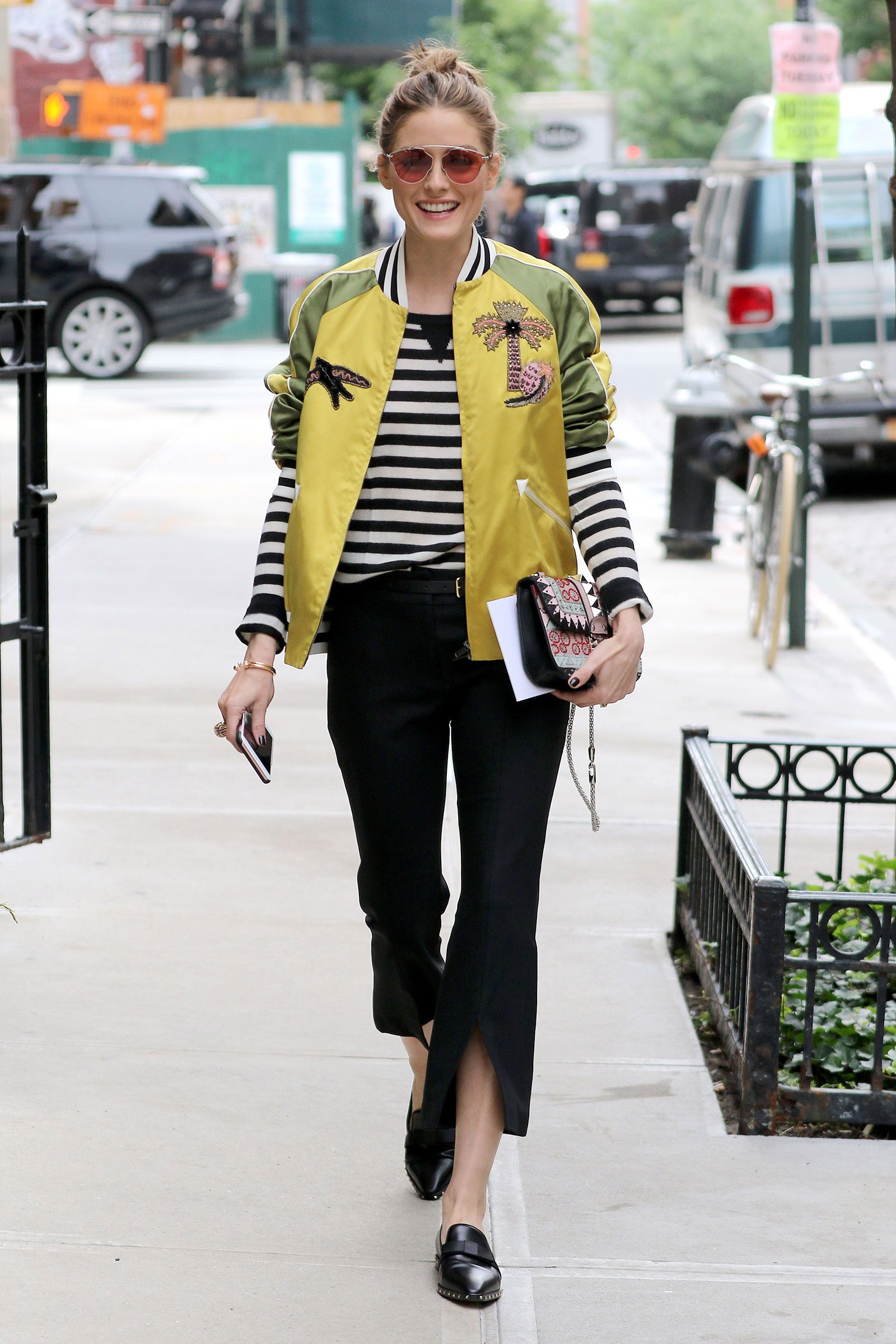 Olivia Palermo wears a yellow satin applique bomber jacket by Valentino with flare cuff pants.