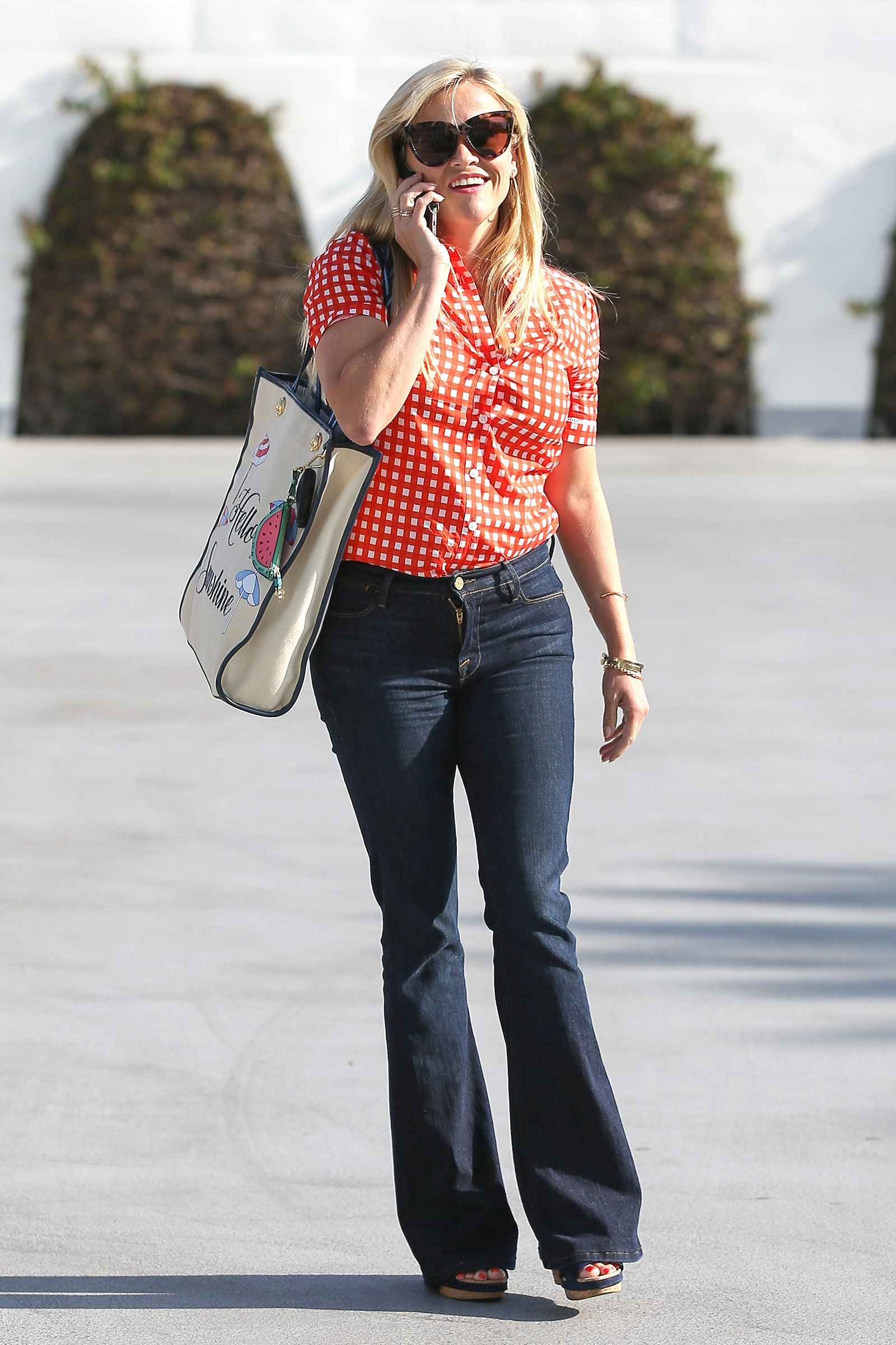 Reese Witherspoon is summery in a red gingham shirt, flare jeans and wedge sandals.