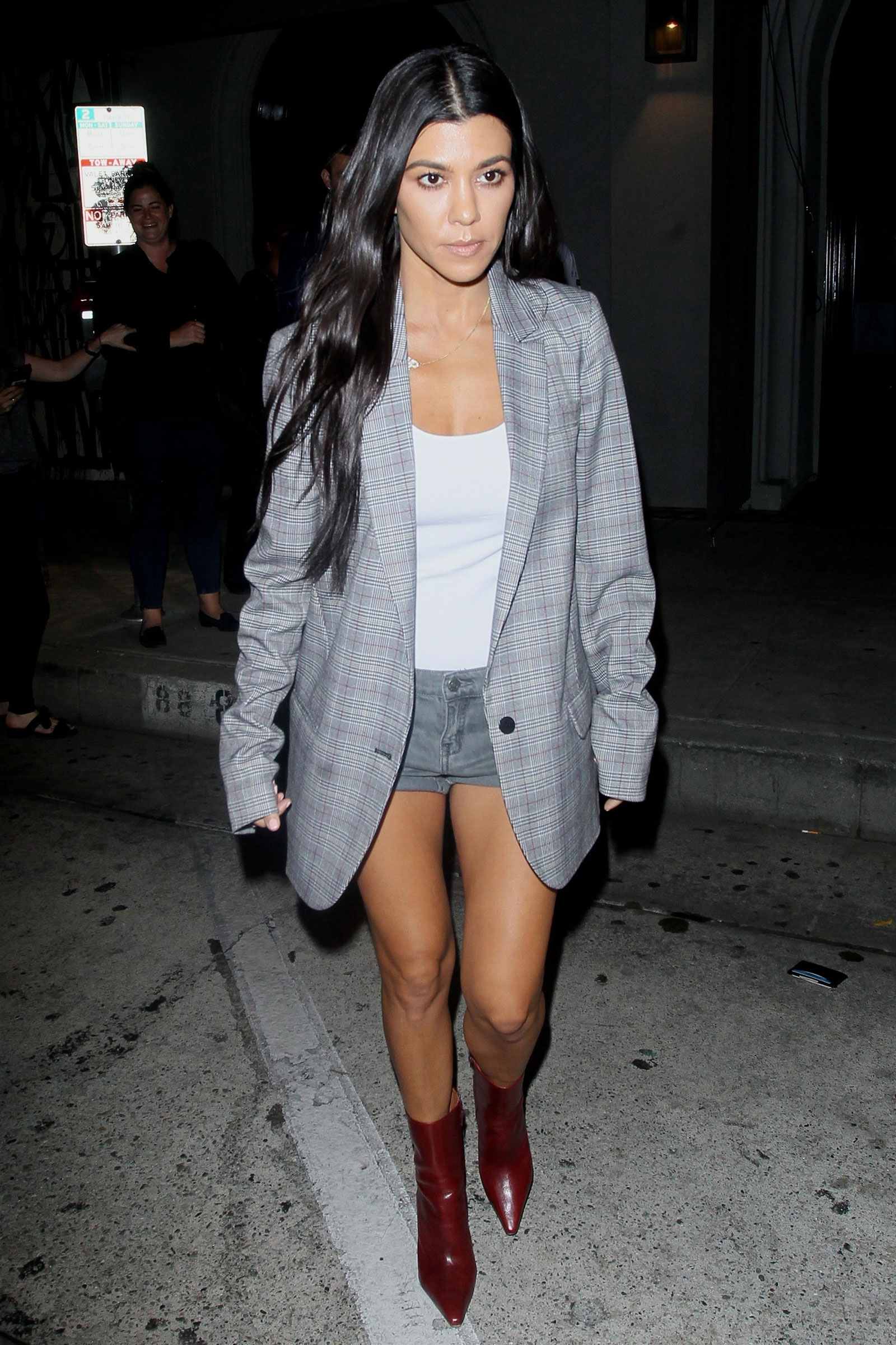 Kourtney Kardashian is seen leaving a restaurant in an oversized blazer, denim shorts and red ankle boots.