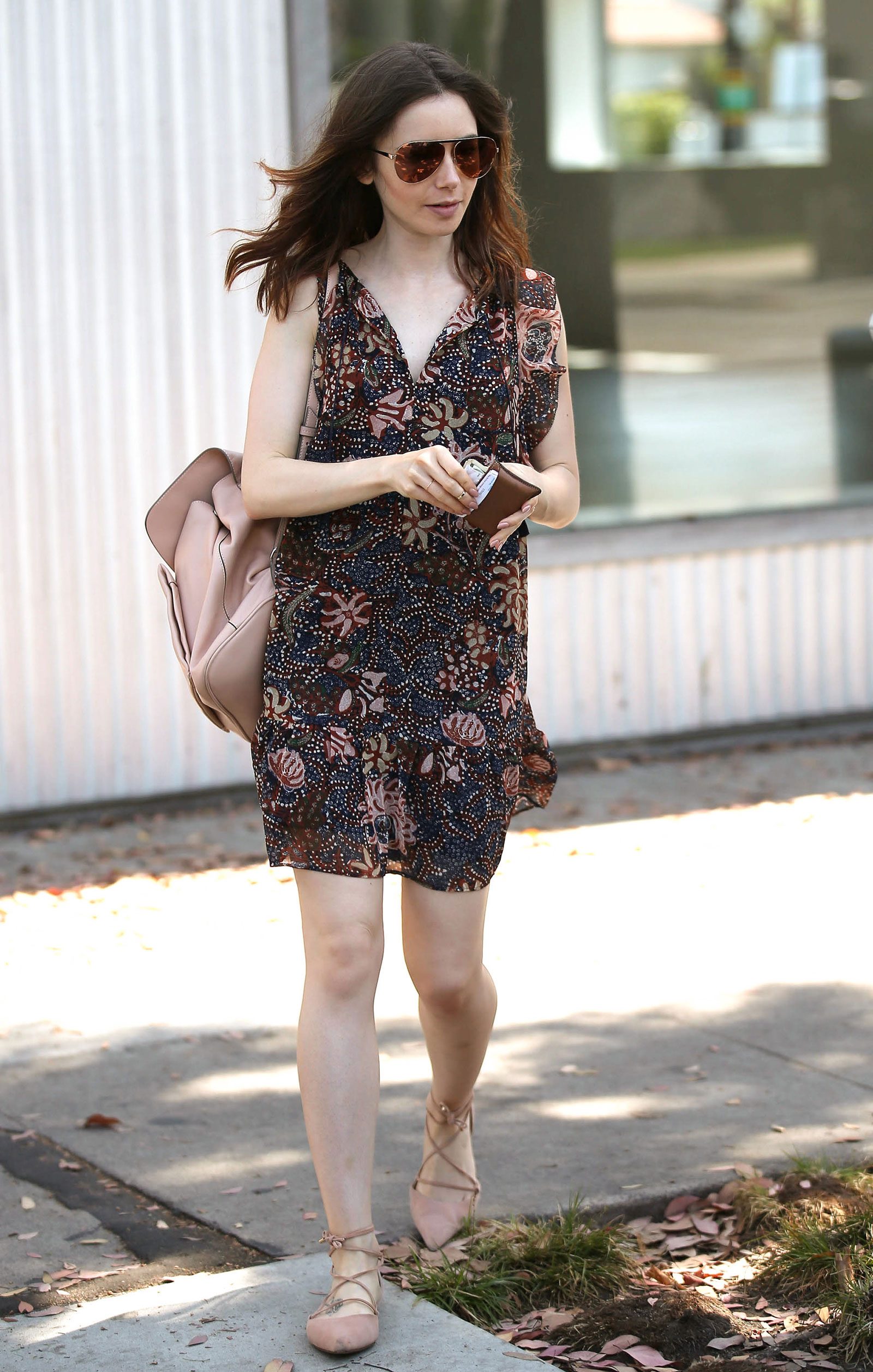 Lily Collins wears the cutest Madewell floral dress (under $100) with blush nude accessories.