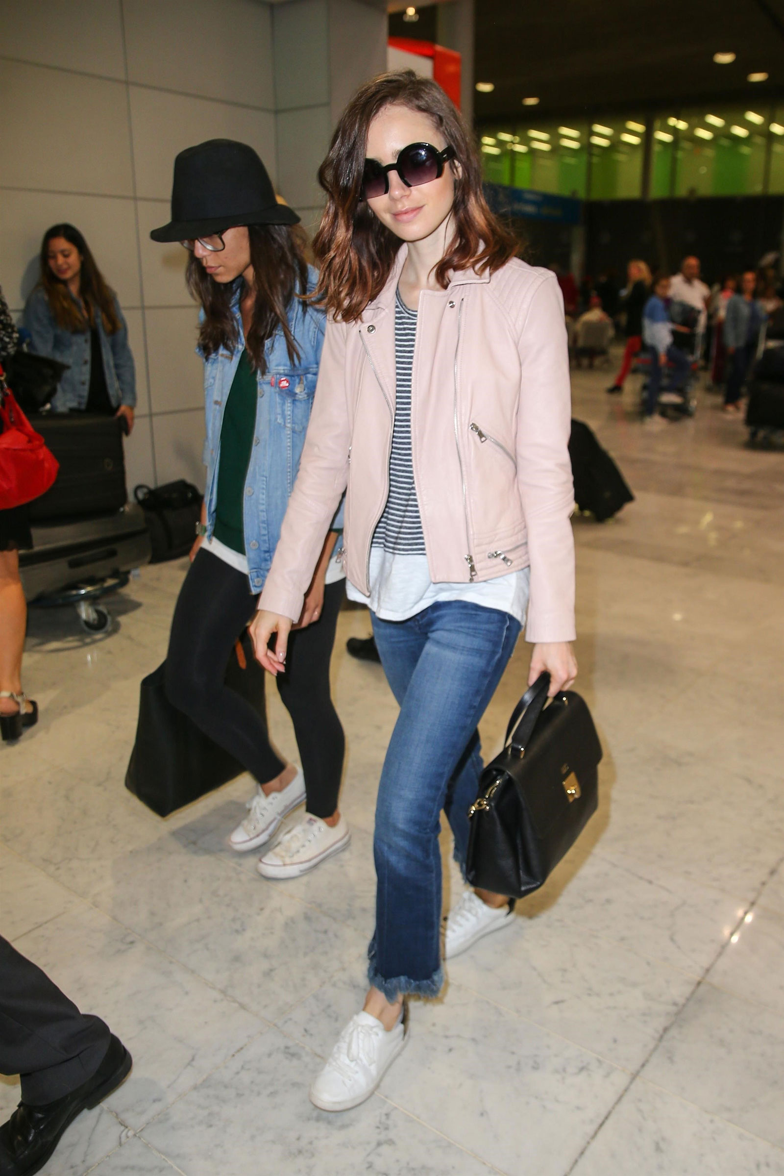 Lily Collins wears a pink moto jacket and stripes.