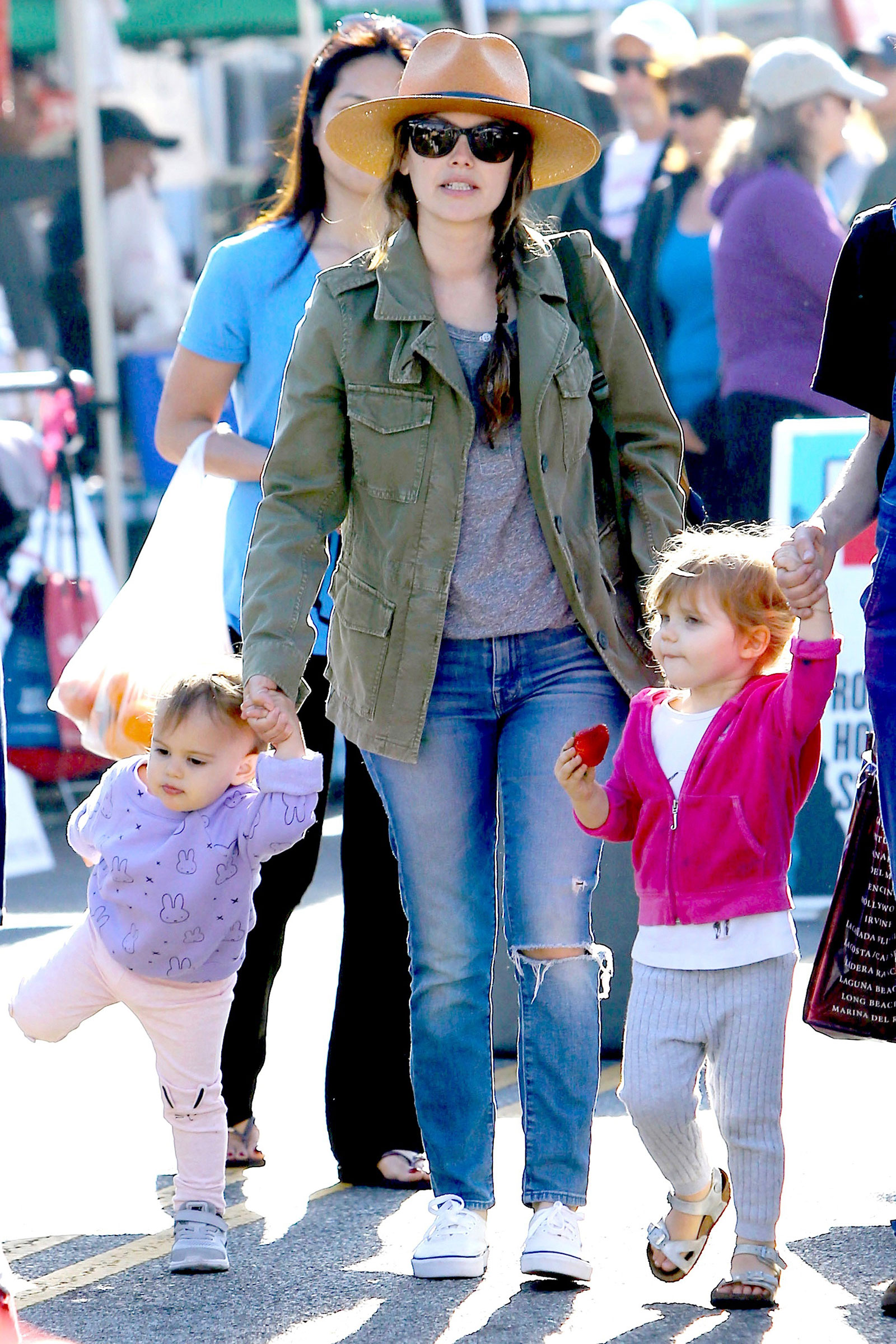 Rachel Bilson's casual mom style is cute and comfy, featuring a utility jacket, ripped jeans and white sneakers.