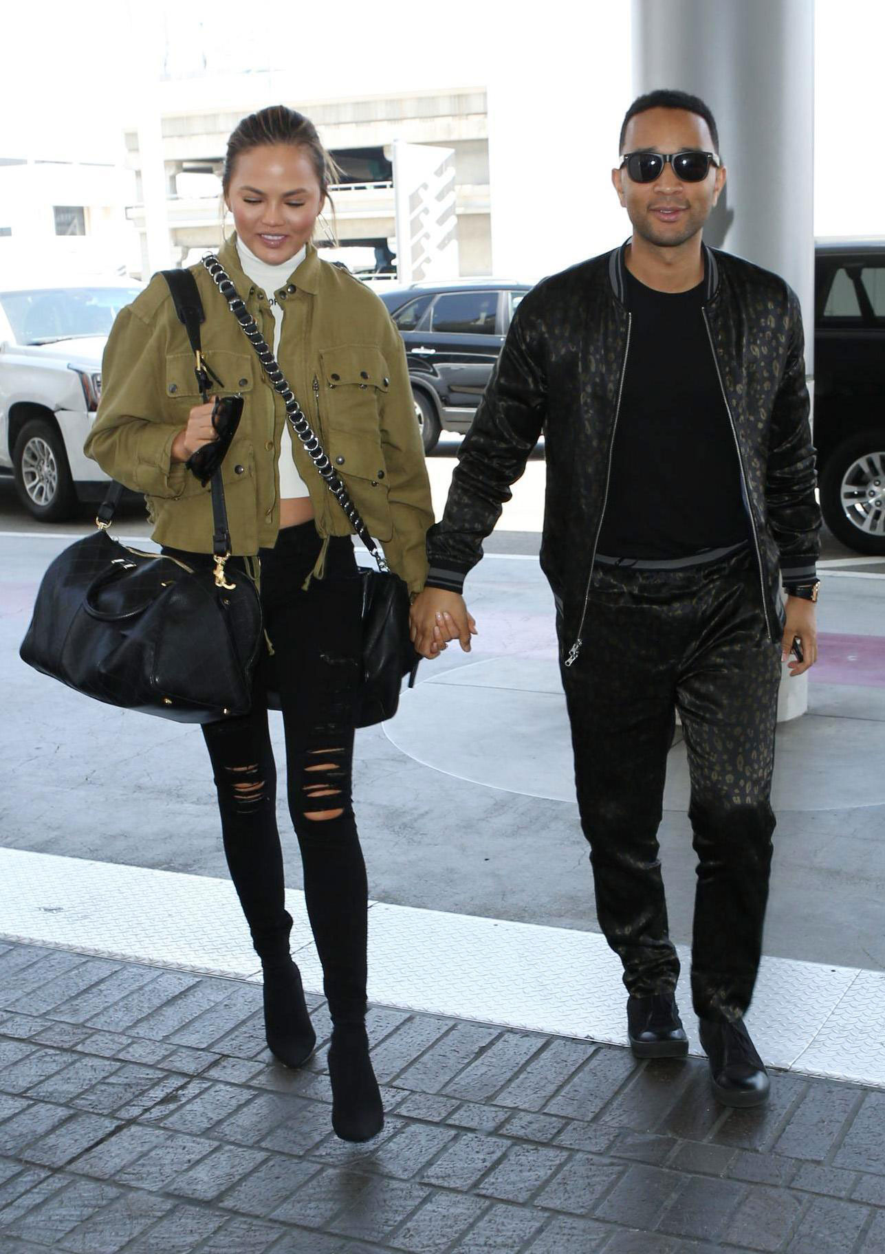 Chrissy Teigen wears a utility jacket with black ripped skinny jeans and ankle boots.