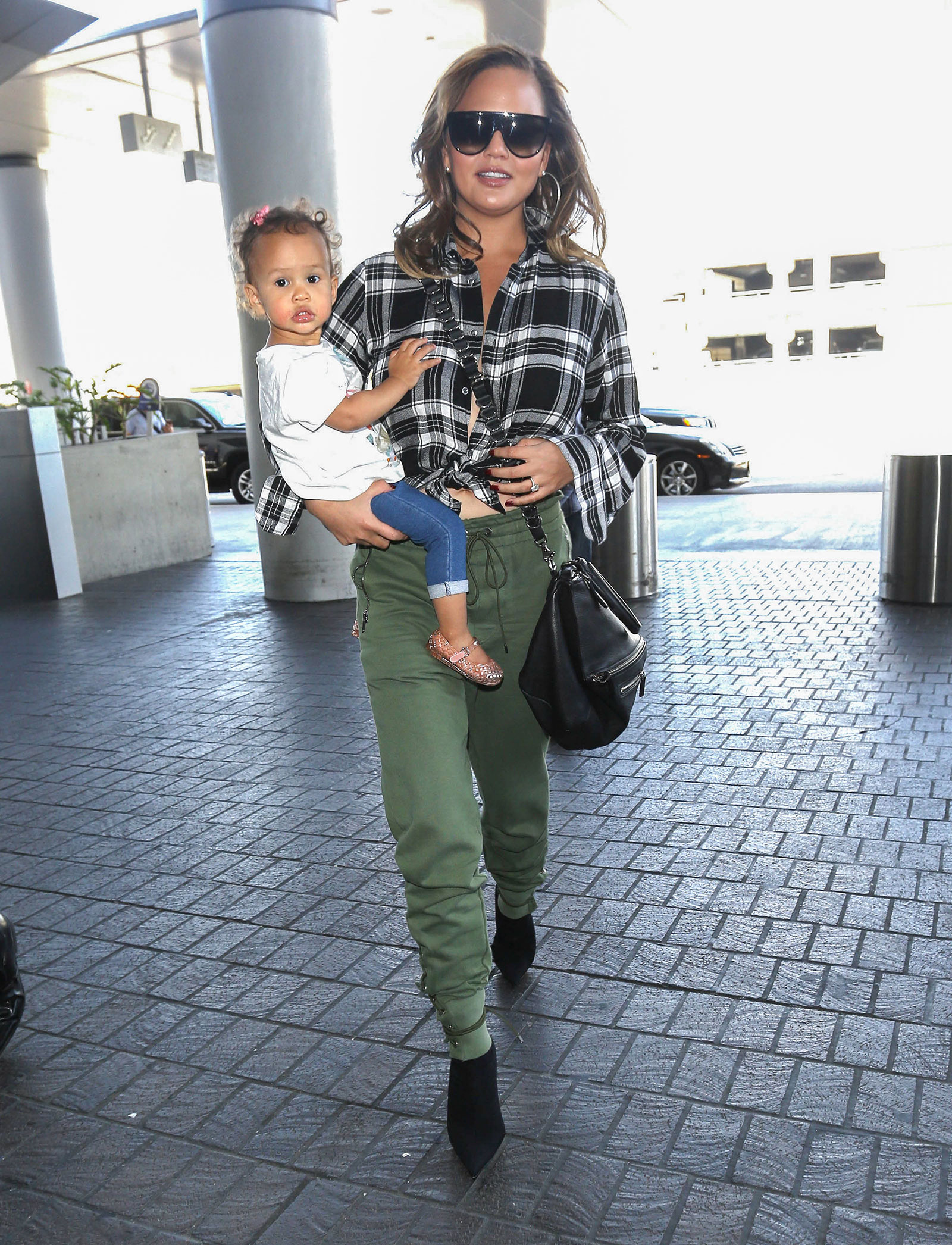 Chrissy Teigen wears a plaid shirt, olive cargo joggers and black stiletto ankle boots.