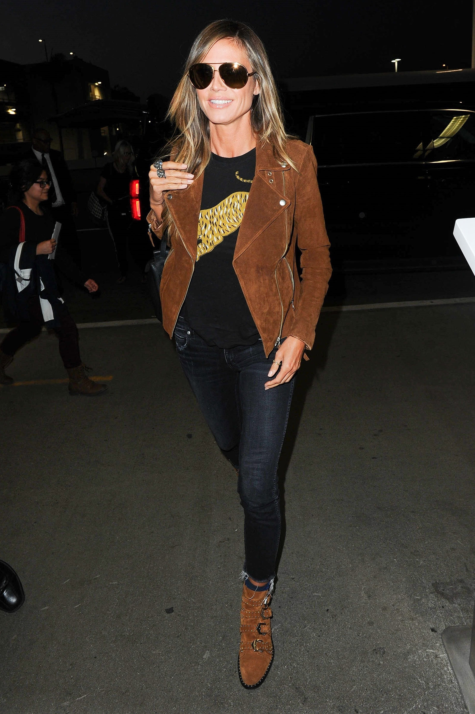 Heidi Klum wears a tan suede moto jacket with black skinny jeans and Givenchy buckled ankle booties.