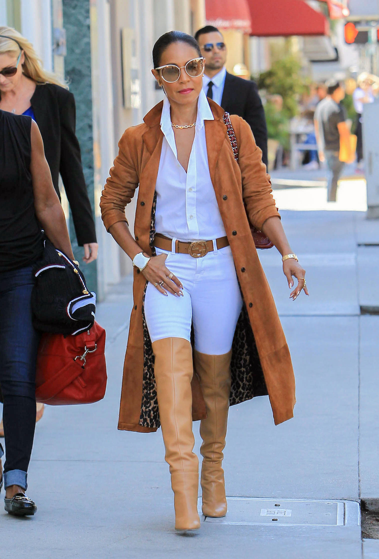 Jada Pinkett Smith wears a camel suede trench coat with a white button-down shirt, white skinny jeans, and cognac over-the-knee boots.