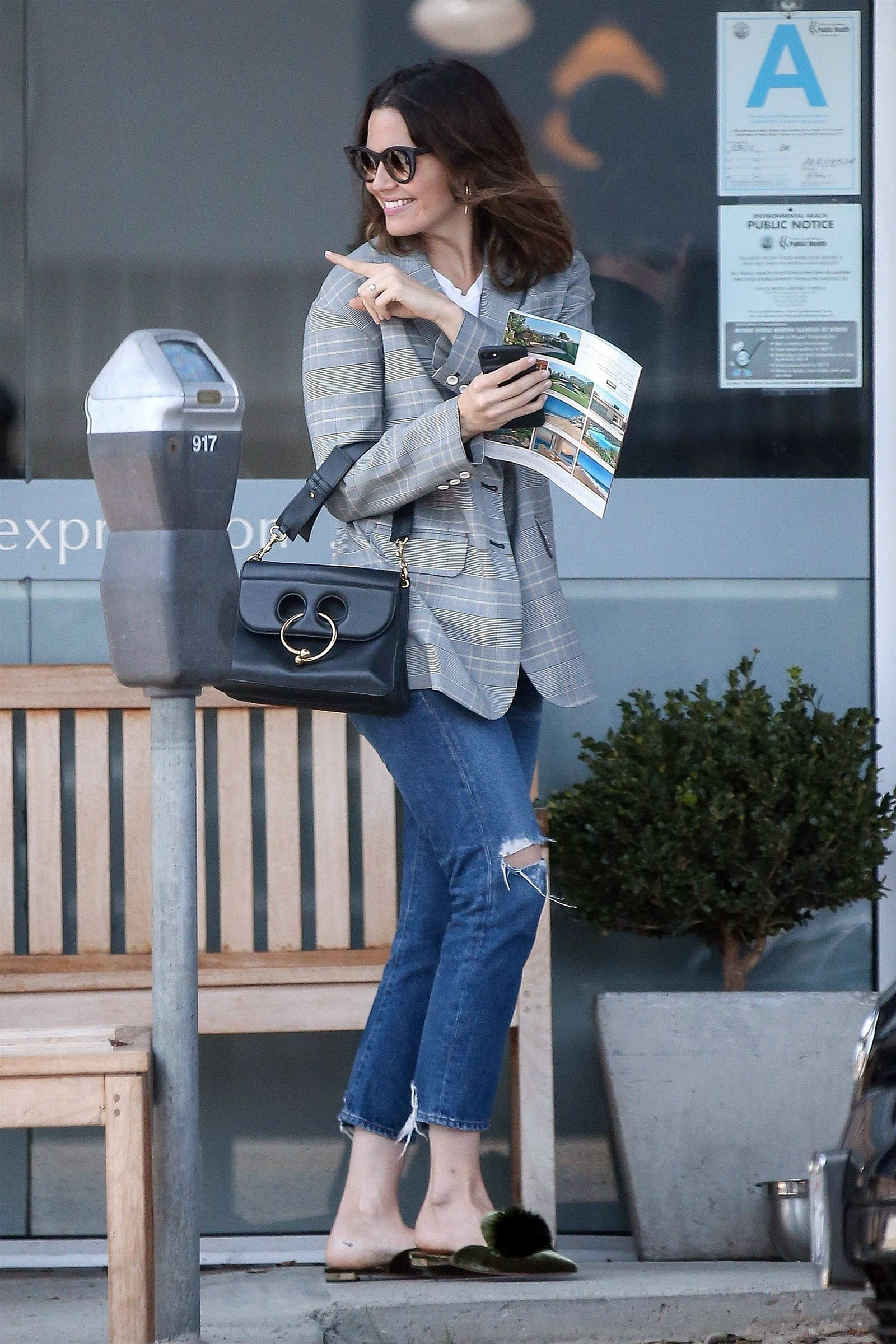 Mandy Moore wears a gray plaid blazer with a white tee, ripped jeans and pom pom fur mules.