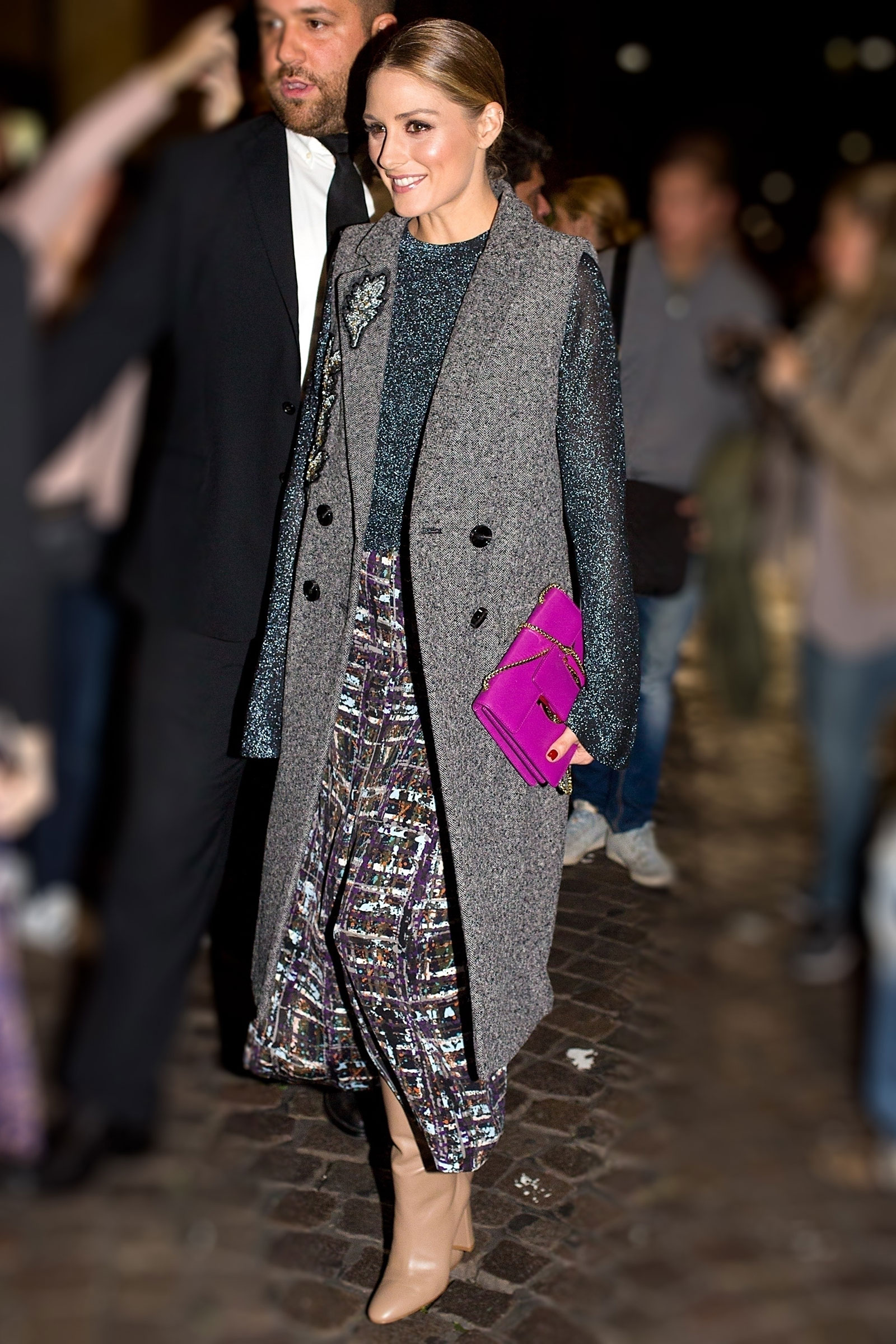 Olivia Palermo wears a sleeveless coat and beige boots at the Ferragamo show in Milan.