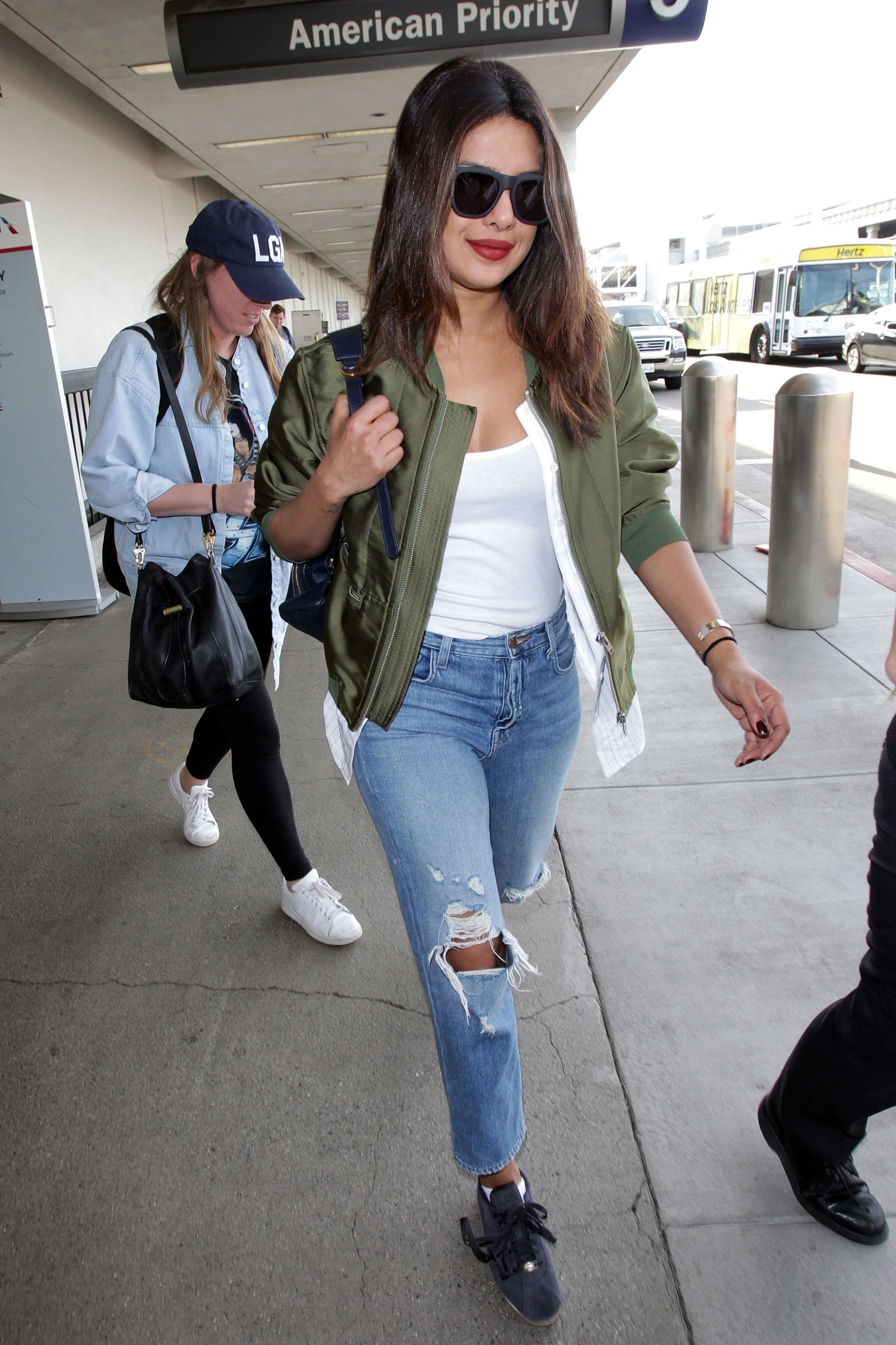 Priyanka Chopra wears a sporty olive green bomber jacket and suede sneakers while traveling through LAX airport.