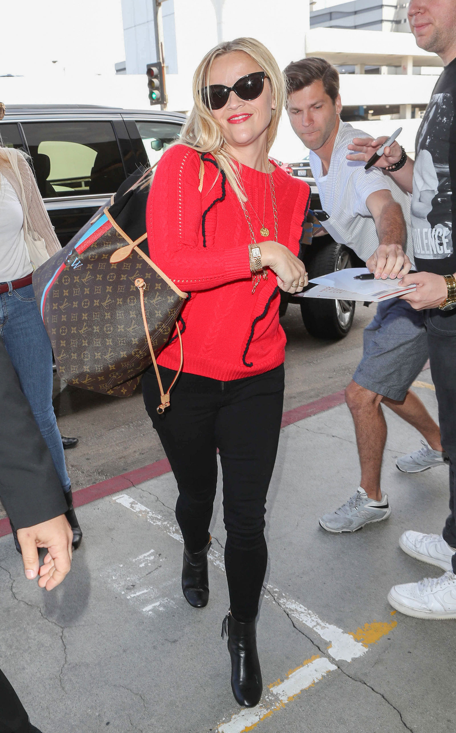 Reese Witherspoon wears a red ruffle sweater by Draper James and carries a Louis Vuitton bag while traveling through LAX.