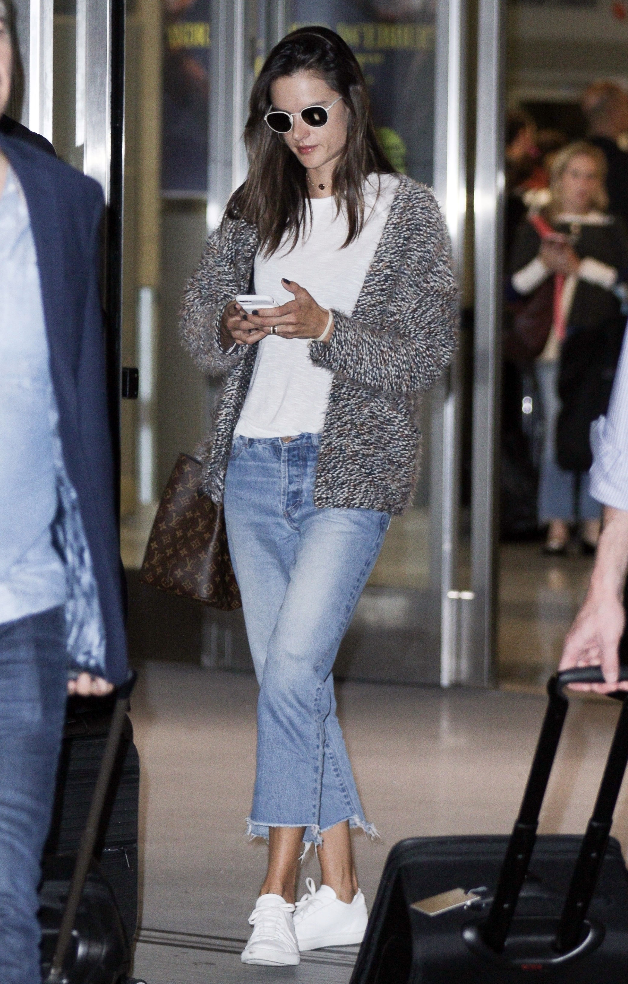 Alessandra Ambrosio wears a chunky knit cardigan with crop jeans and white sneakers while traveling through the airport.
