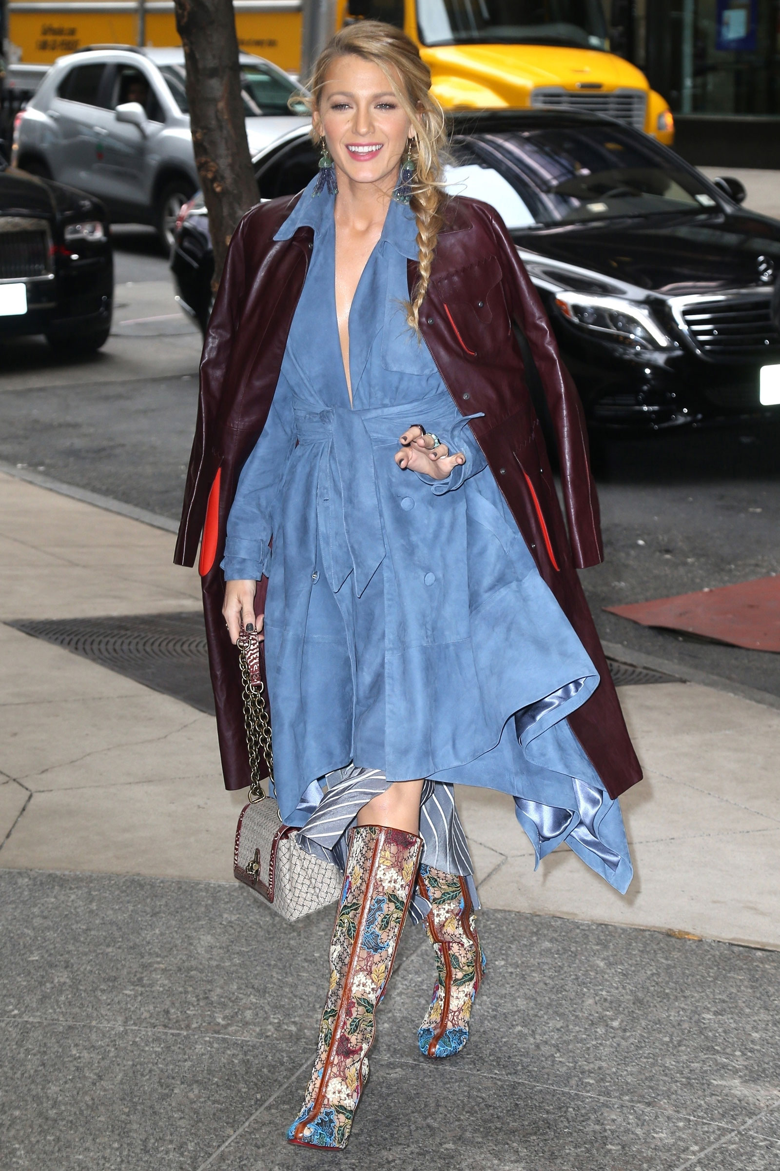 Blake Lively wears a Bottega Veneta burgundy leather trench coat, denim wrap dress and Christian Louboutin embroidered boots.