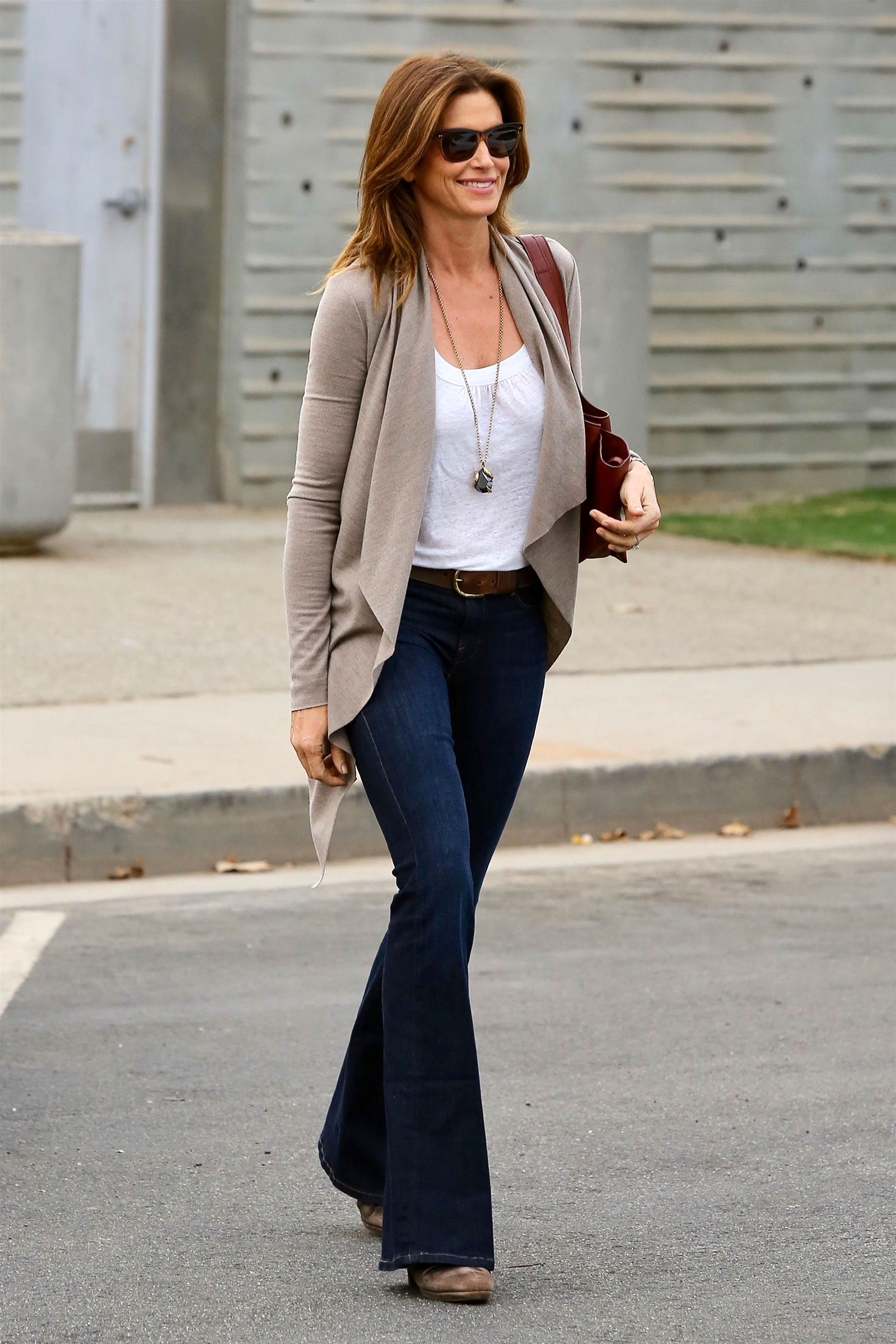 0b20b7d7f0 Cindy Crawford looks stylish in a beige cardigan and flare leg jeans while  running errands in