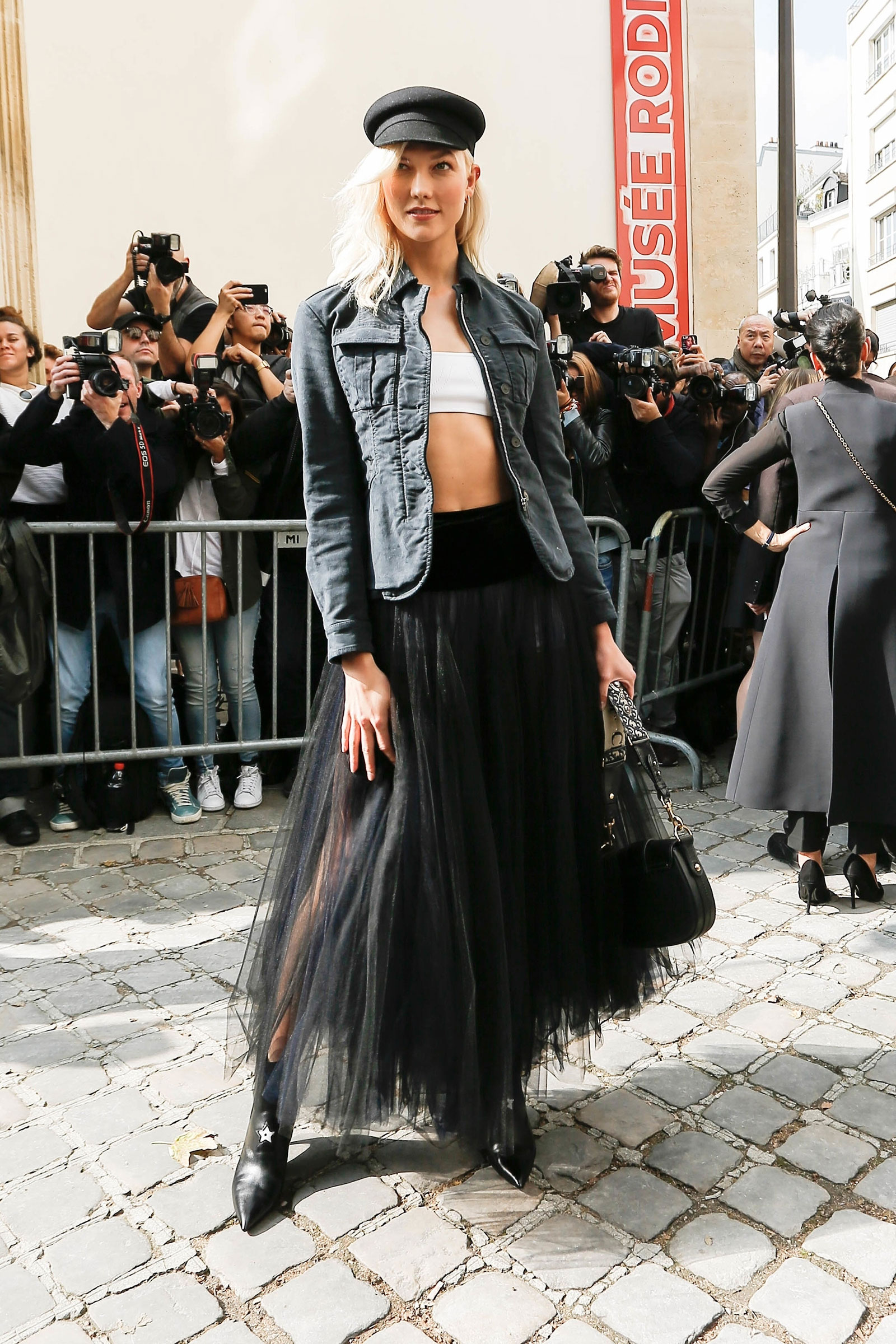 Karlie Kloss arrives at the Dior Paris fashion week show in a tulle skirt and zipper jacket.