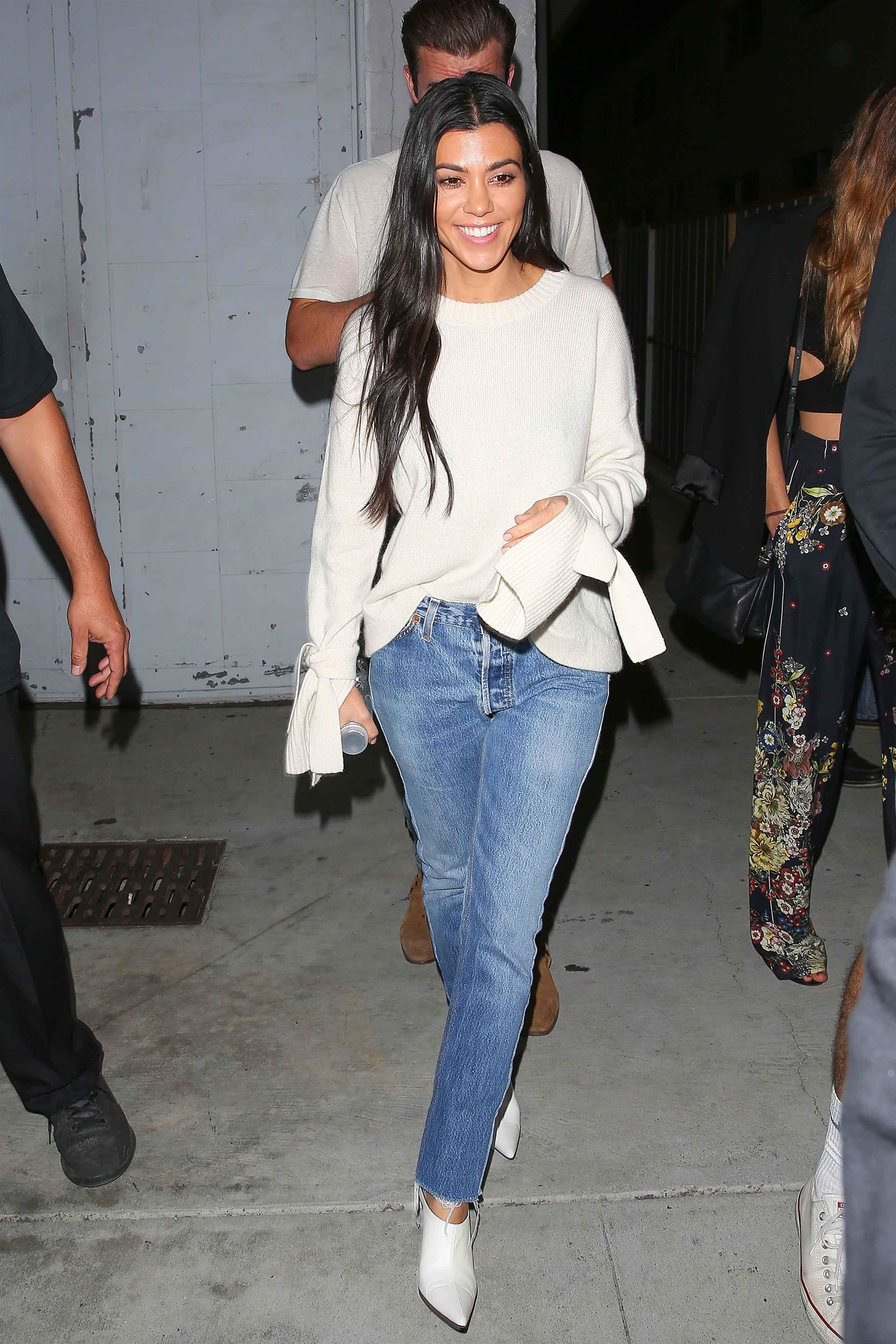 Kourtney Kardashian wears a cream bell sleeve sweater with crop step hem jeans and white mules.