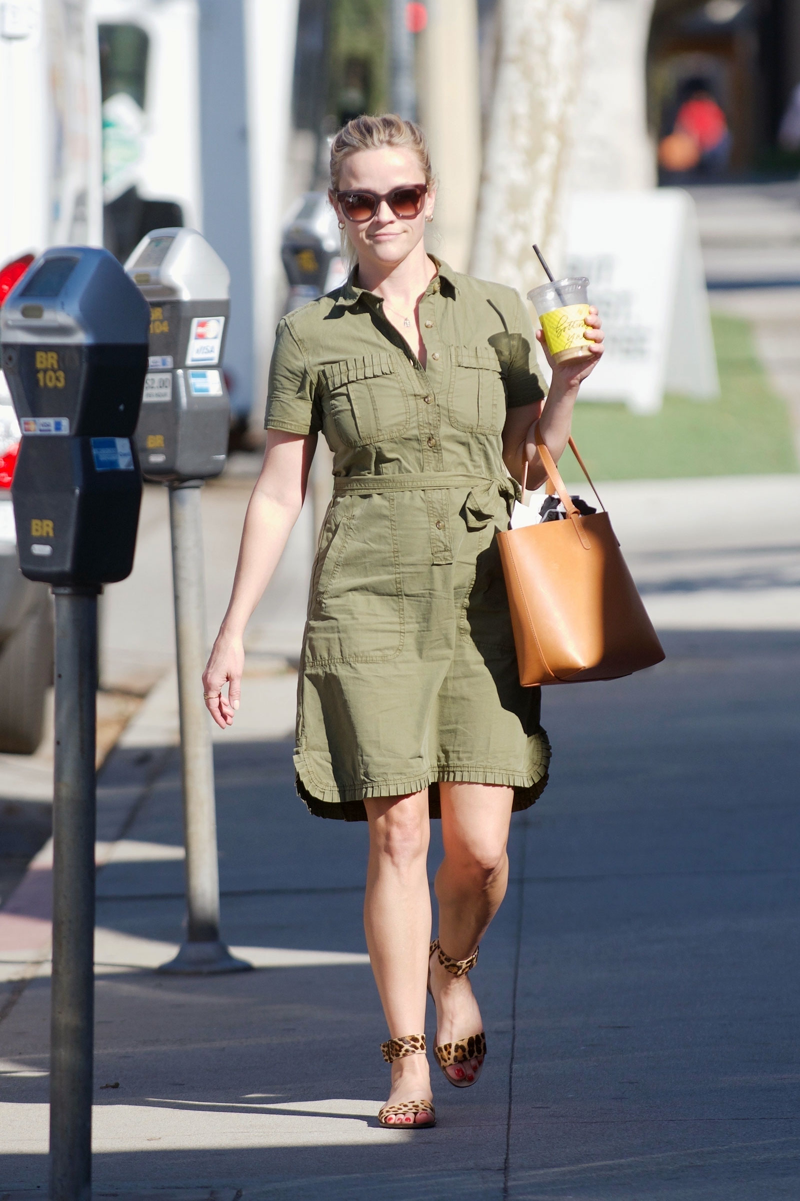 Reese Witherspoon wears an olive green ruffle trim J.Crew shirtdress with leopard sandals and a brown leather tote bag.