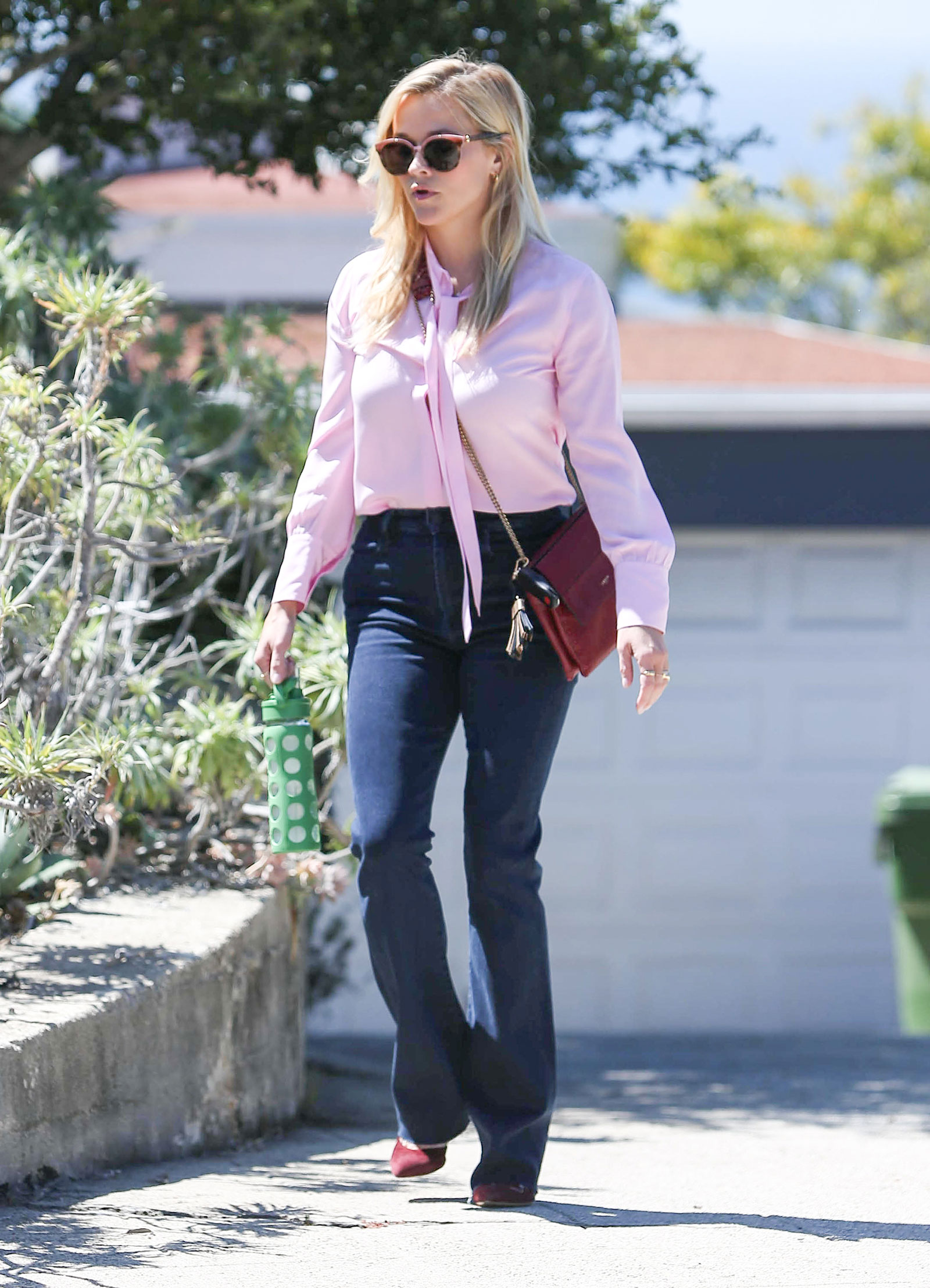 Reese Witherspoon pink blouse flare jeans burgundy pumps celebrity style