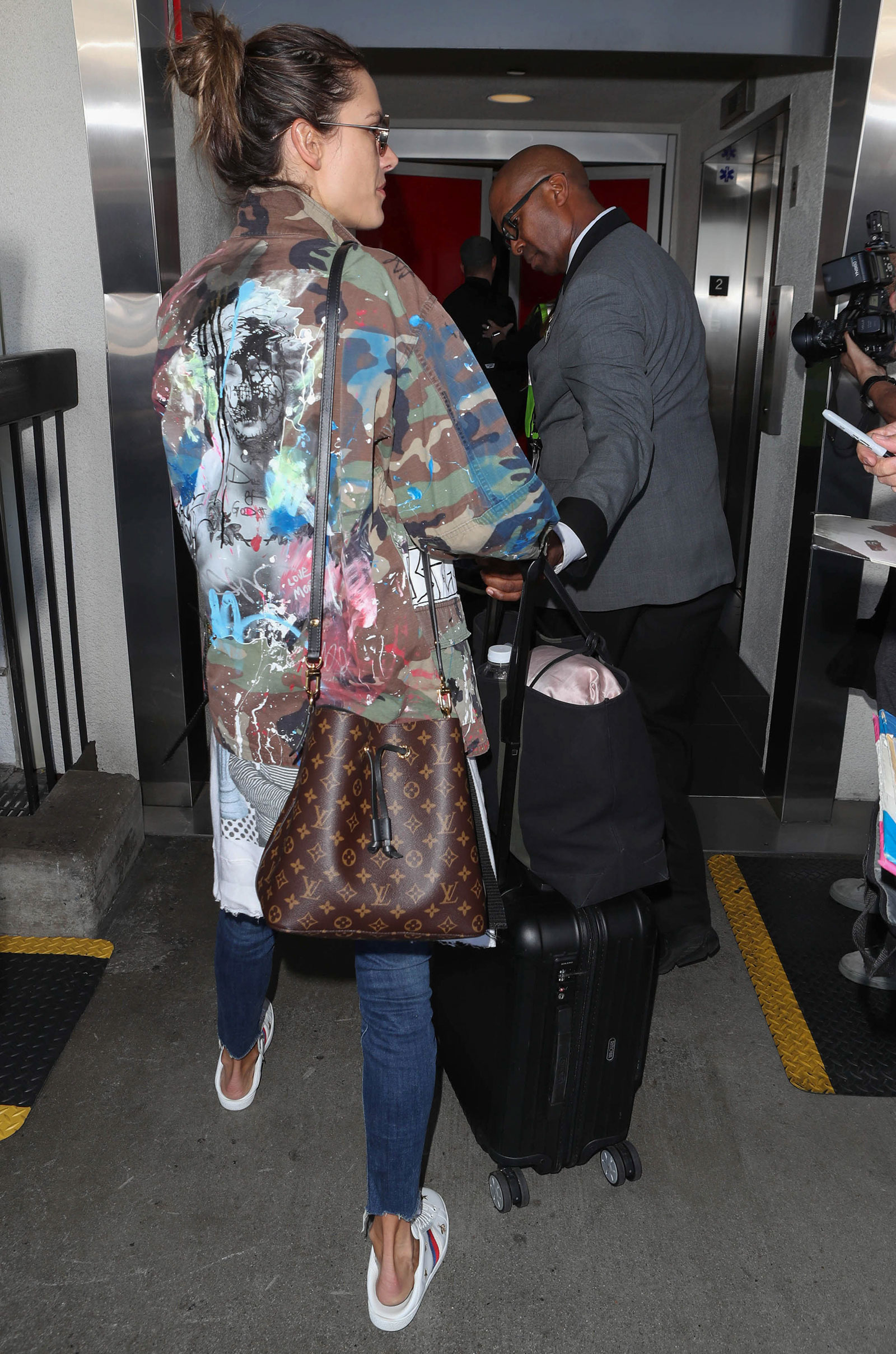 Alessandra Ambrosio wears a camo shirt with white crop top, distressed Mother jeans and Gucci backless Ace sneakers while traveling through LAX.