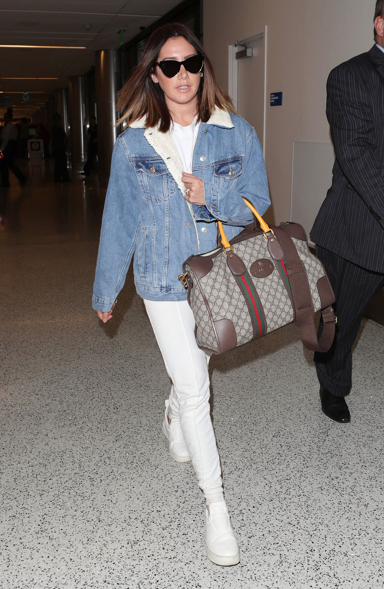 Ashley Tisdale wears a denim jacket with sherpa lining, white tracksuit and Gucci weekender bag