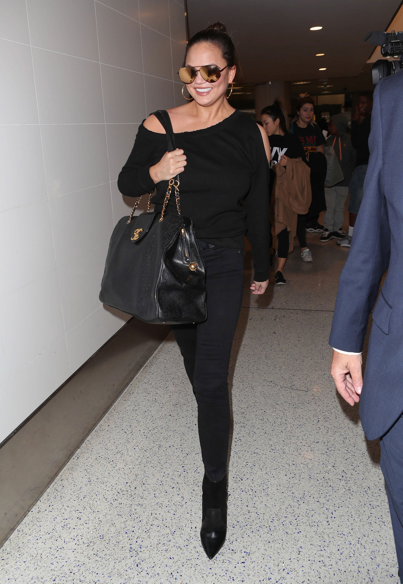 81b1c420a3994b Chrissy Teigen wears a cold shoulder top and Chanel bag while traveling.
