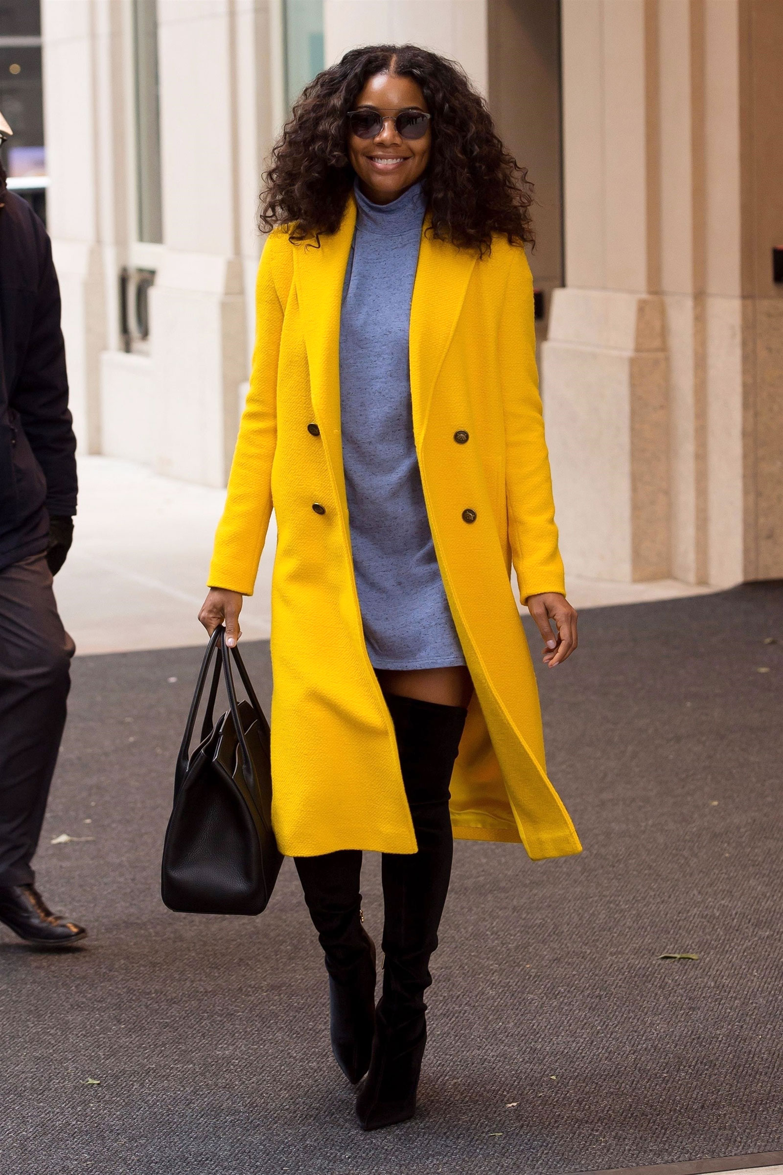 Gabrielle Union wears a bright yellow wool coat with a gray sweatedress and black over-the-knee boots.