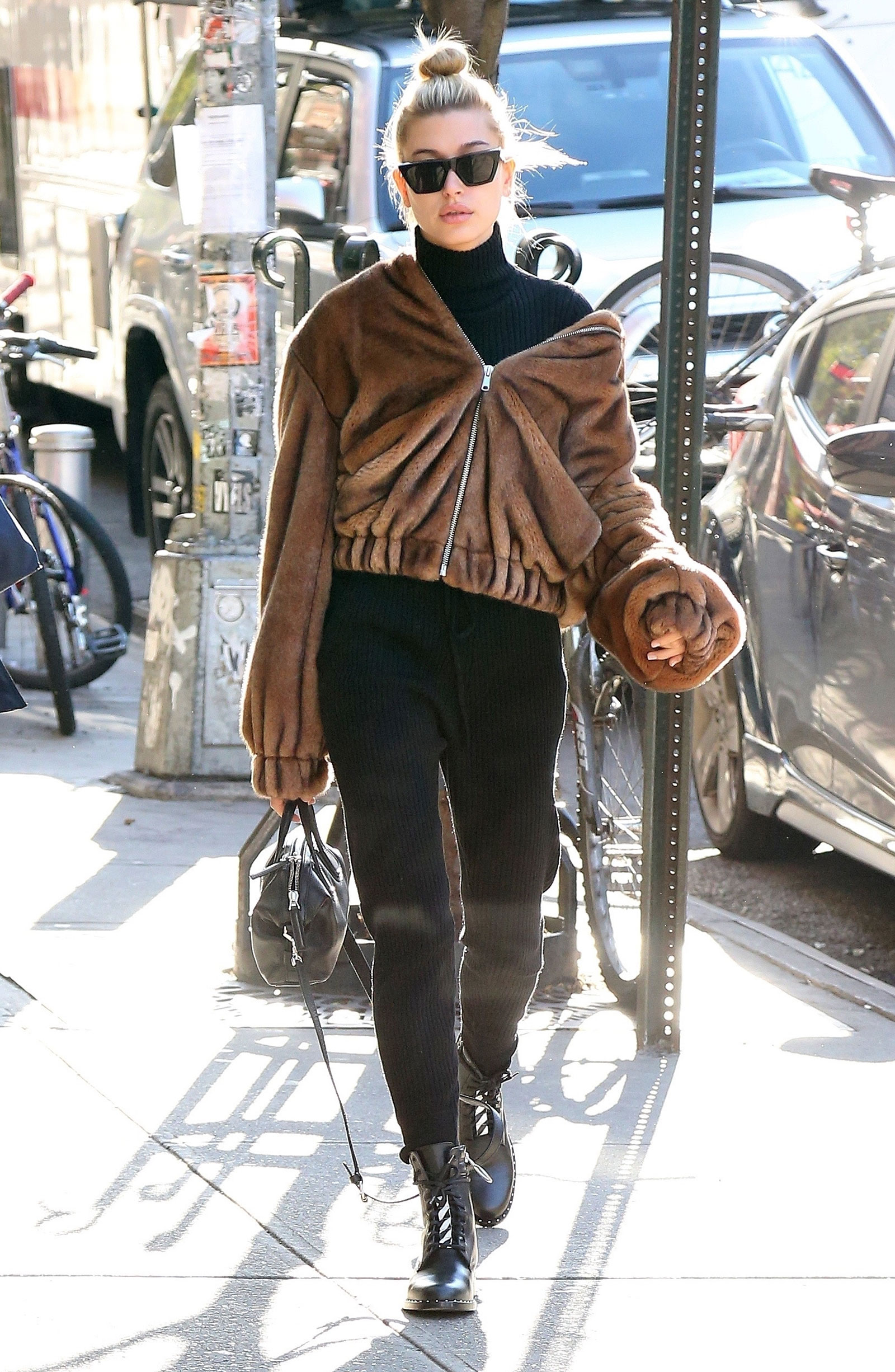 Hailey Baldwin wears Helmut Lang faux fur bomber jacket with Off White combat boots.